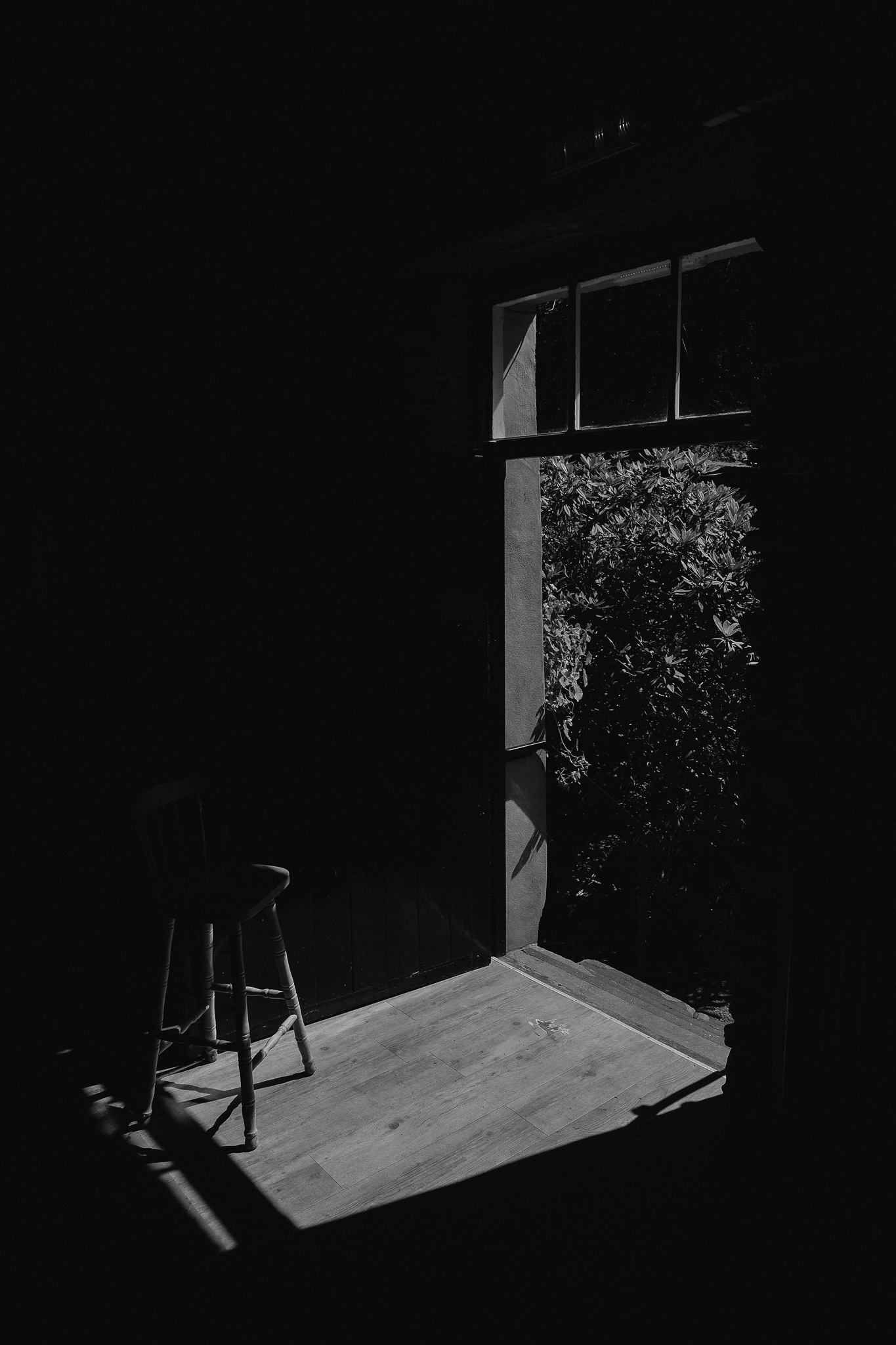 Black and white photo of a chair holding open a door while summer sun spills through the doorway