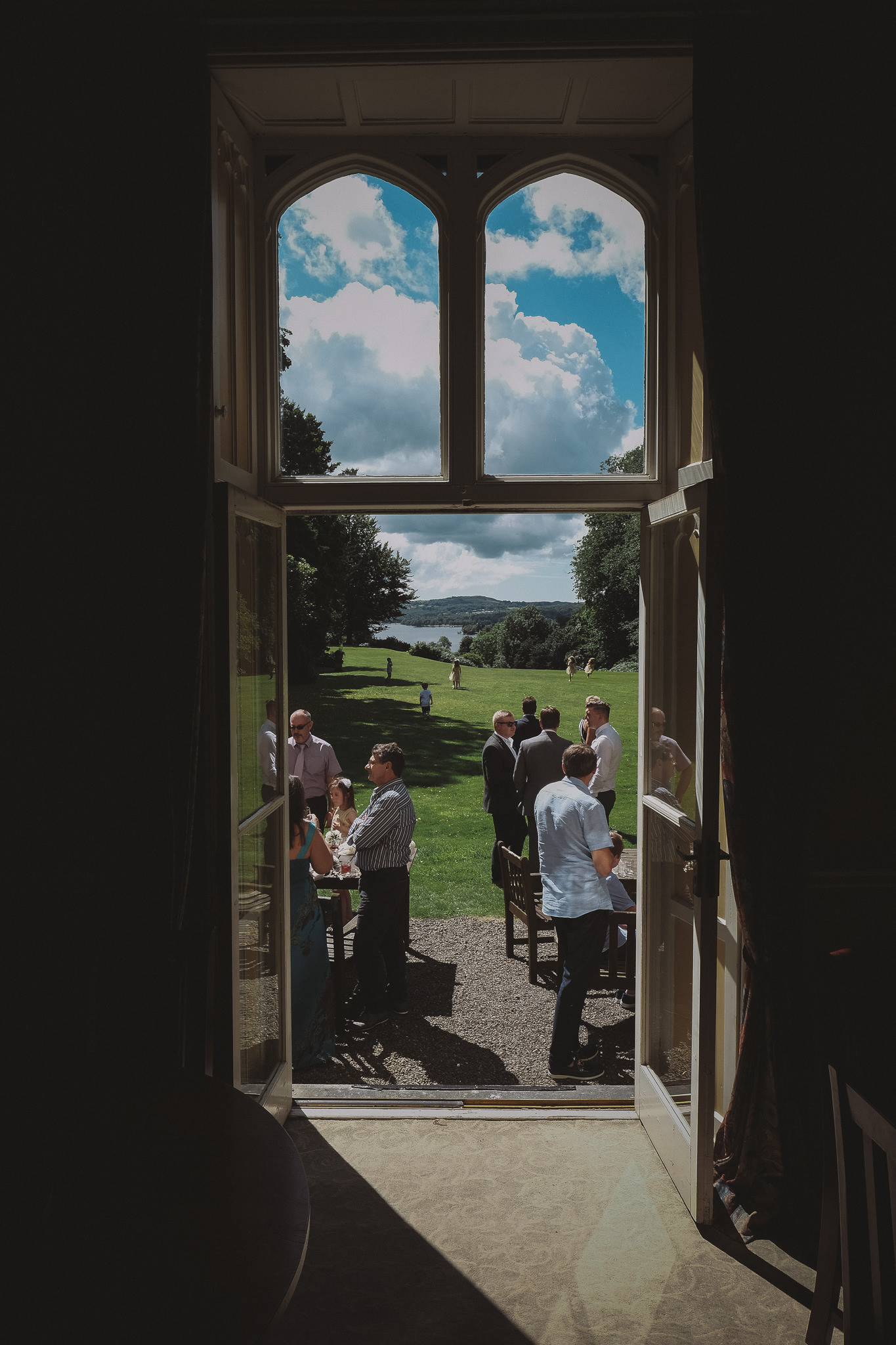 Photo of wedding guests in the sunshine, seen through a doorway in the Lake District