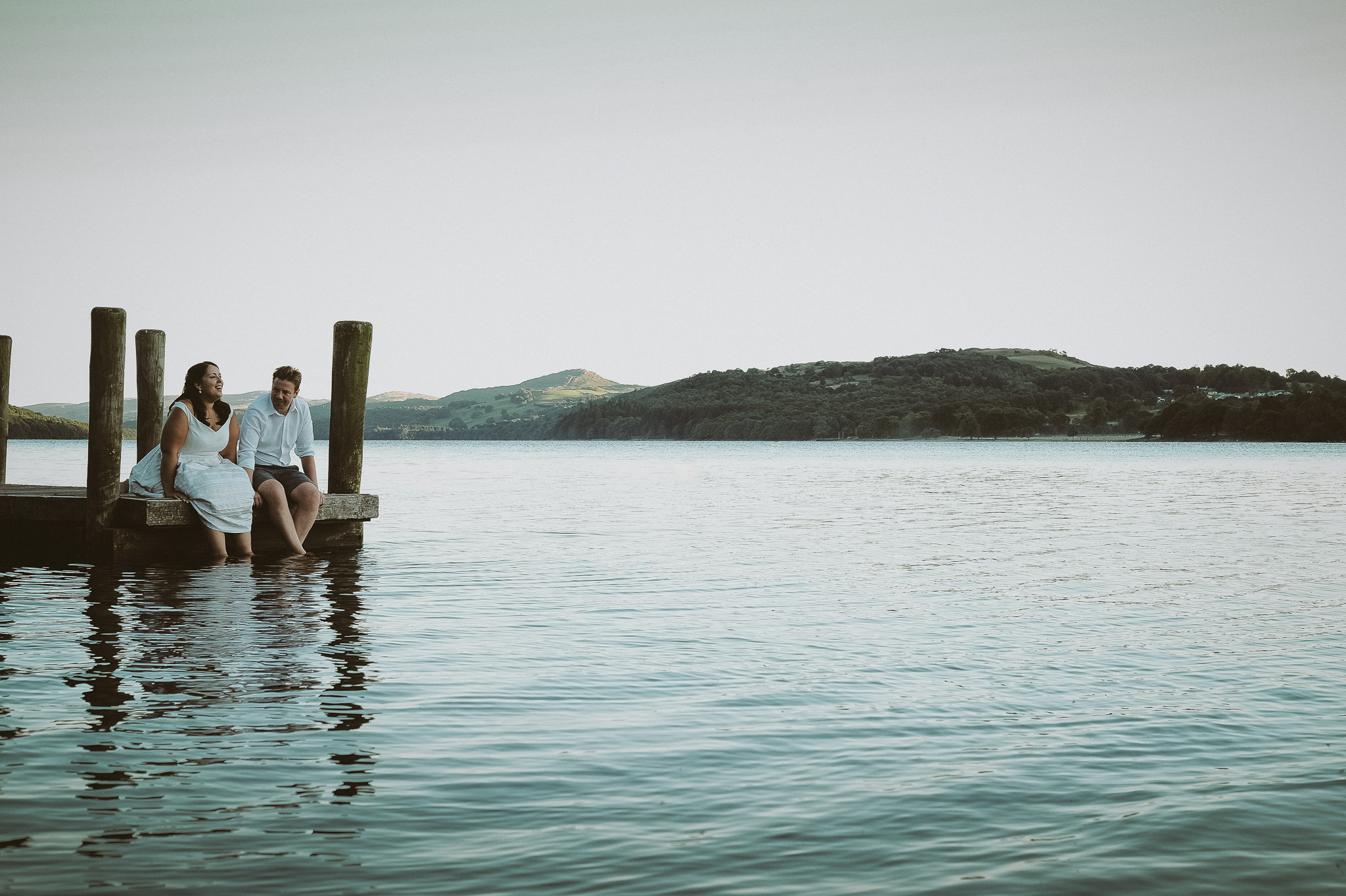 Bride and groom sit on a jetty on Coniston Lake