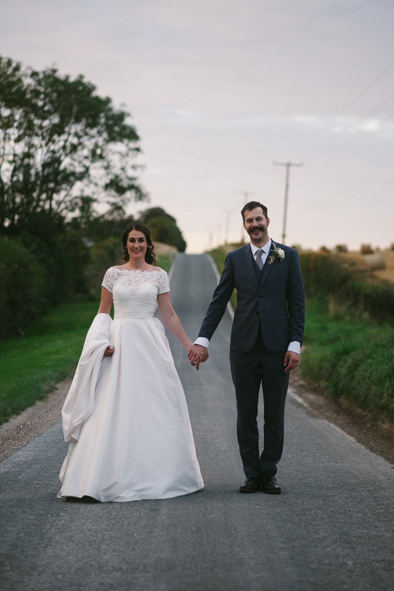 Bride and groom hold hands in the middle of the road