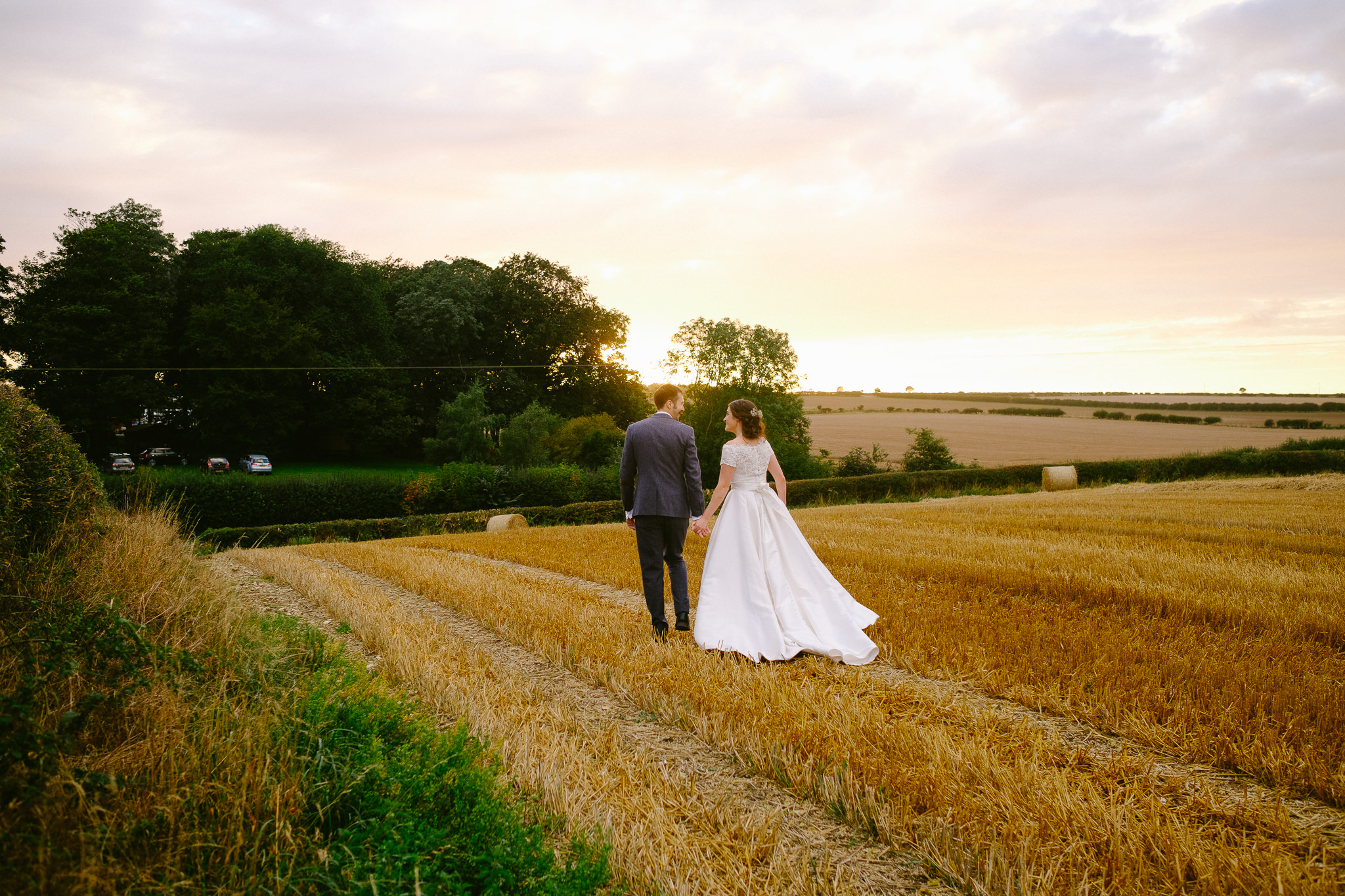 Bride and groom walk through a wheat field in Yorkshire