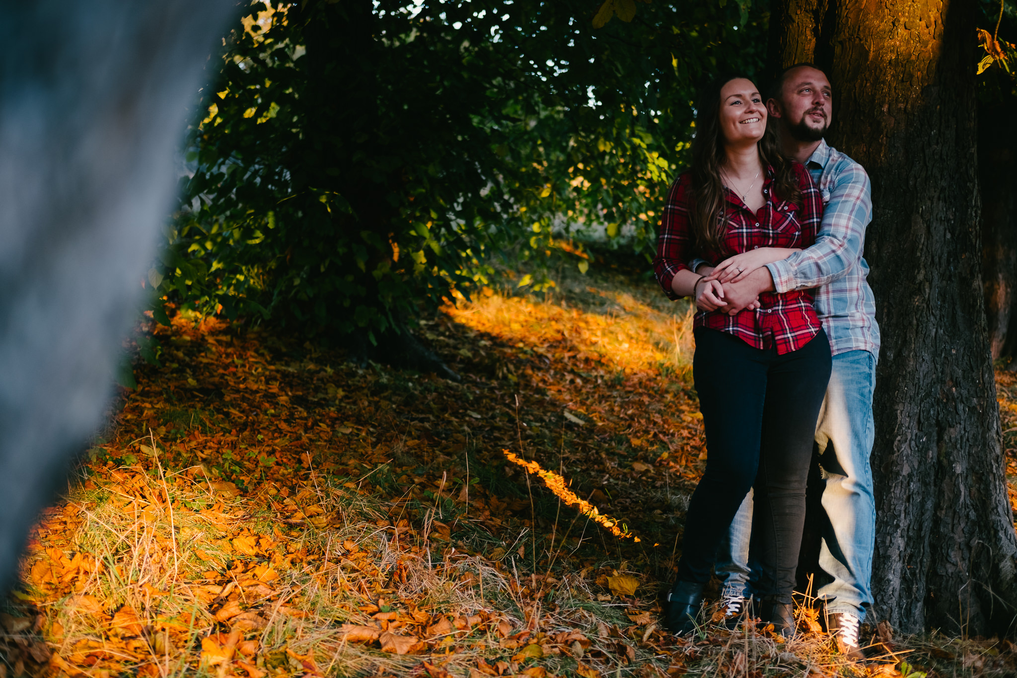 Couple cuddle in warm autumn sunlight on Sunderland pre-wedding photoshoot