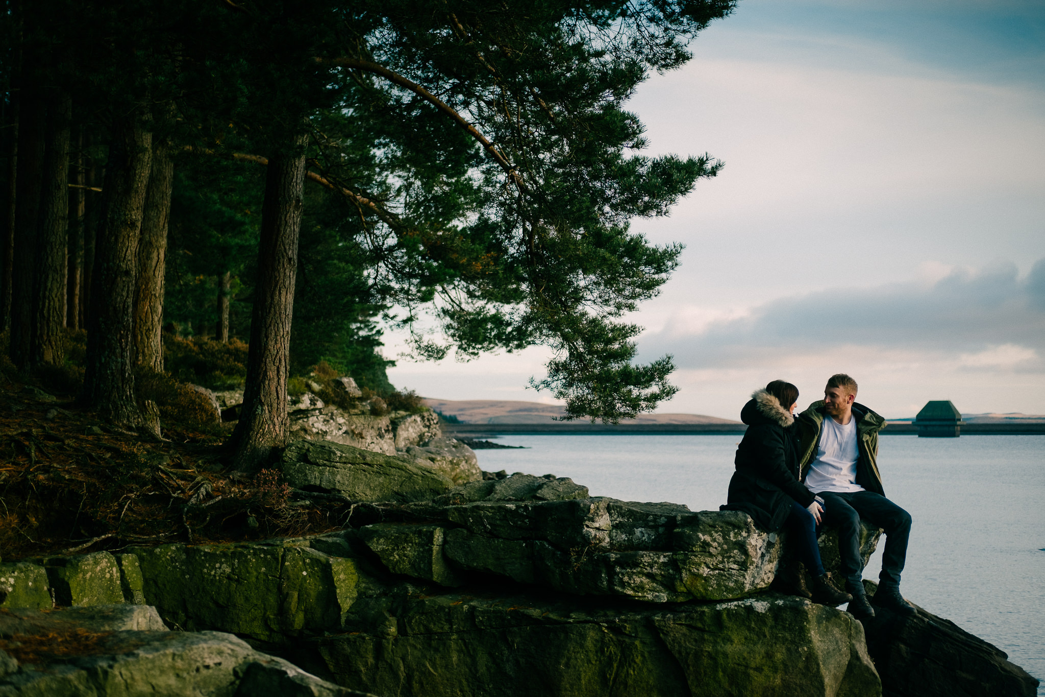 Couple sit on rocks with Kielder Forest in the background