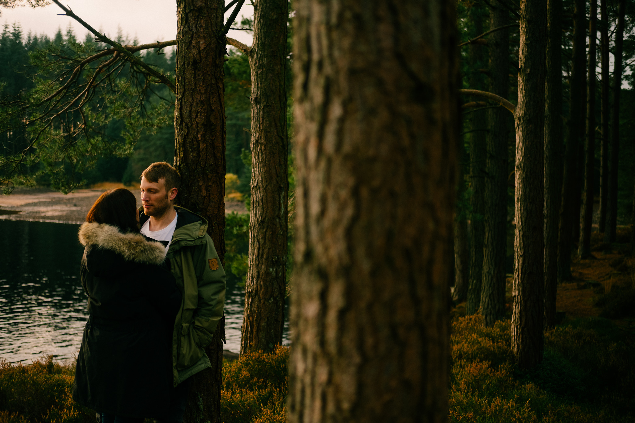 Engaged couple cuddle in Kielder Forest
