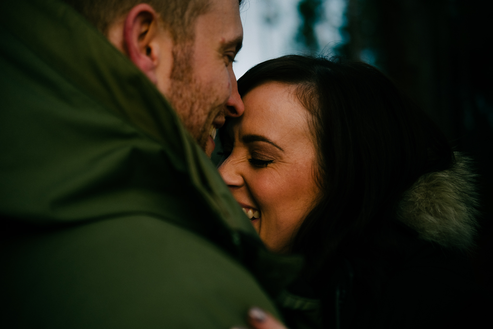 Close up of engaged couple laughing in Kielder Forest