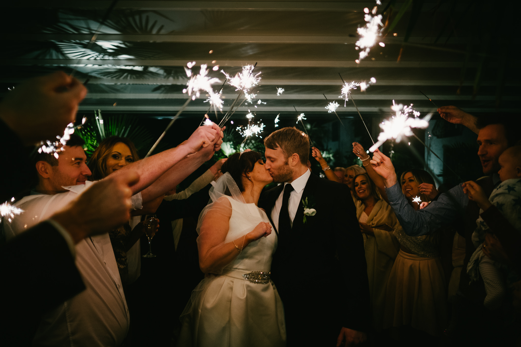 Bride and groom kiss under sparklers at le petit chateau