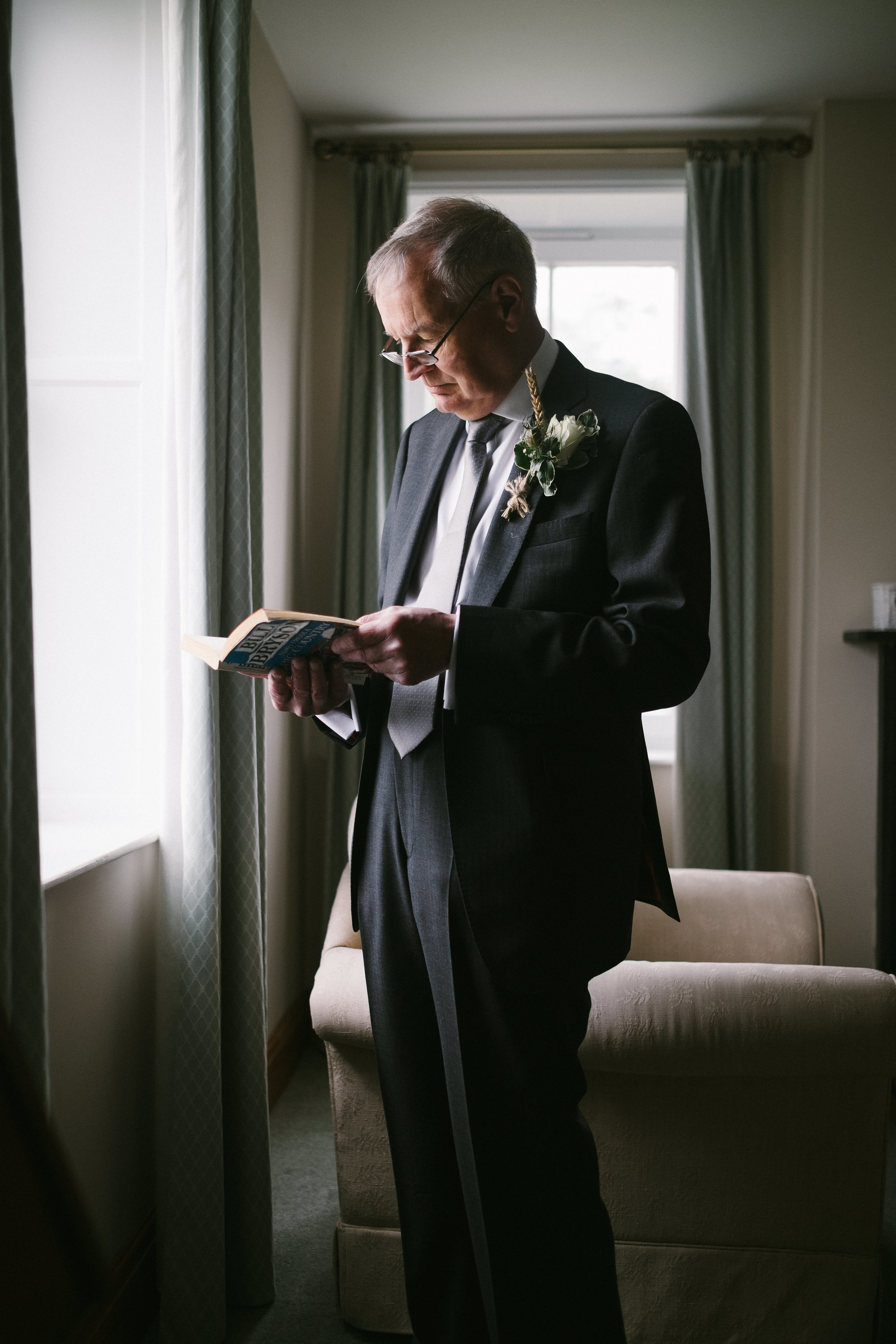 Father of the groom reads a book while standing at a window before his son's wedding