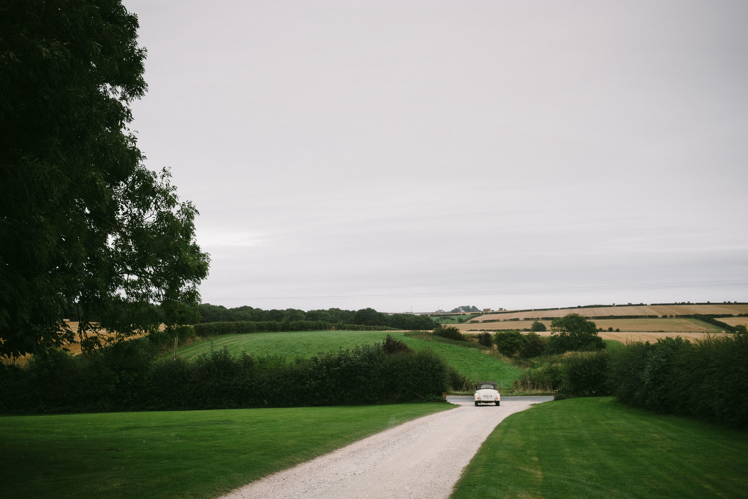 Bride drives off to church with the rolling hills of Yorkshire in background