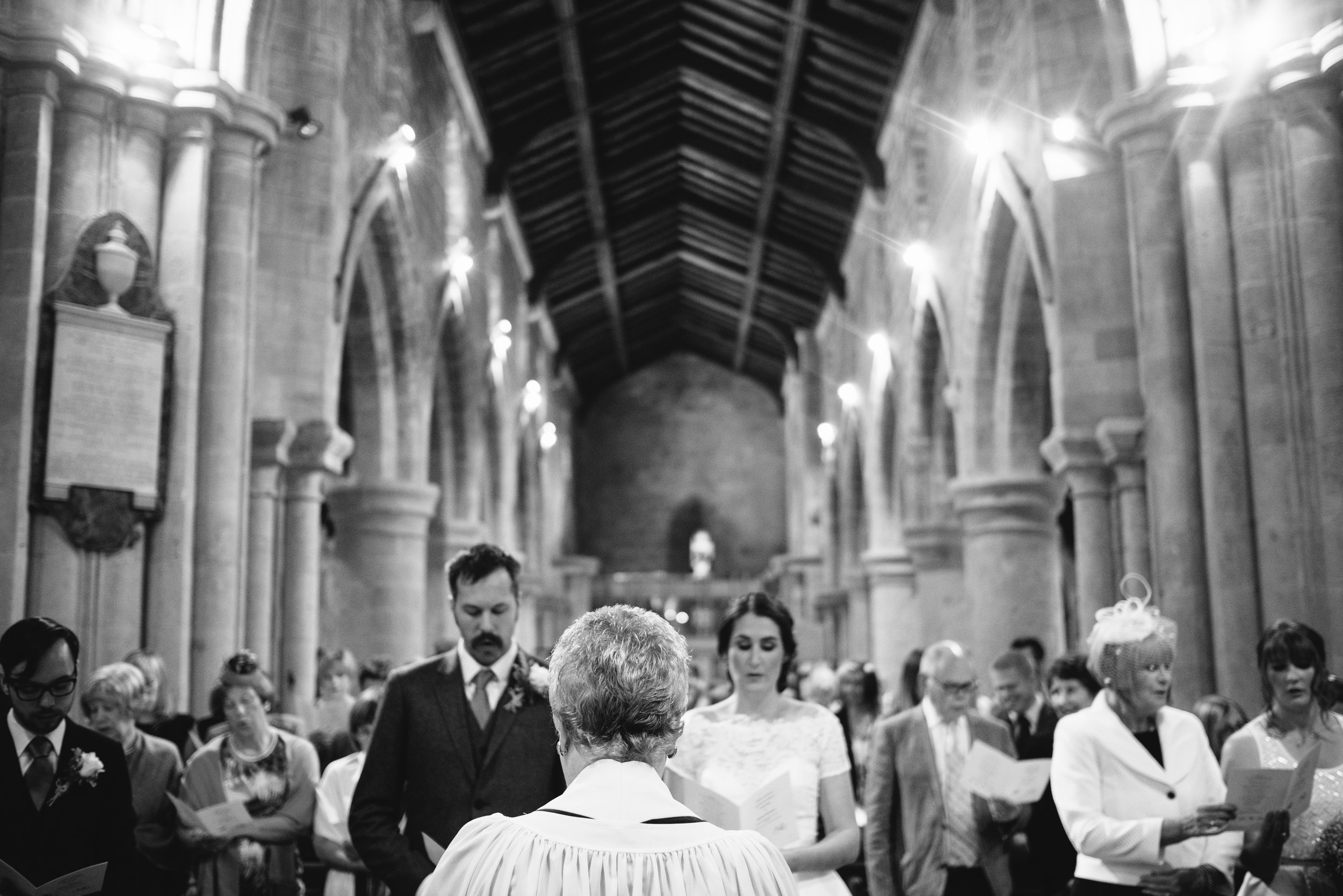 Black and white photo of the celebrant conducting the wedding in church
