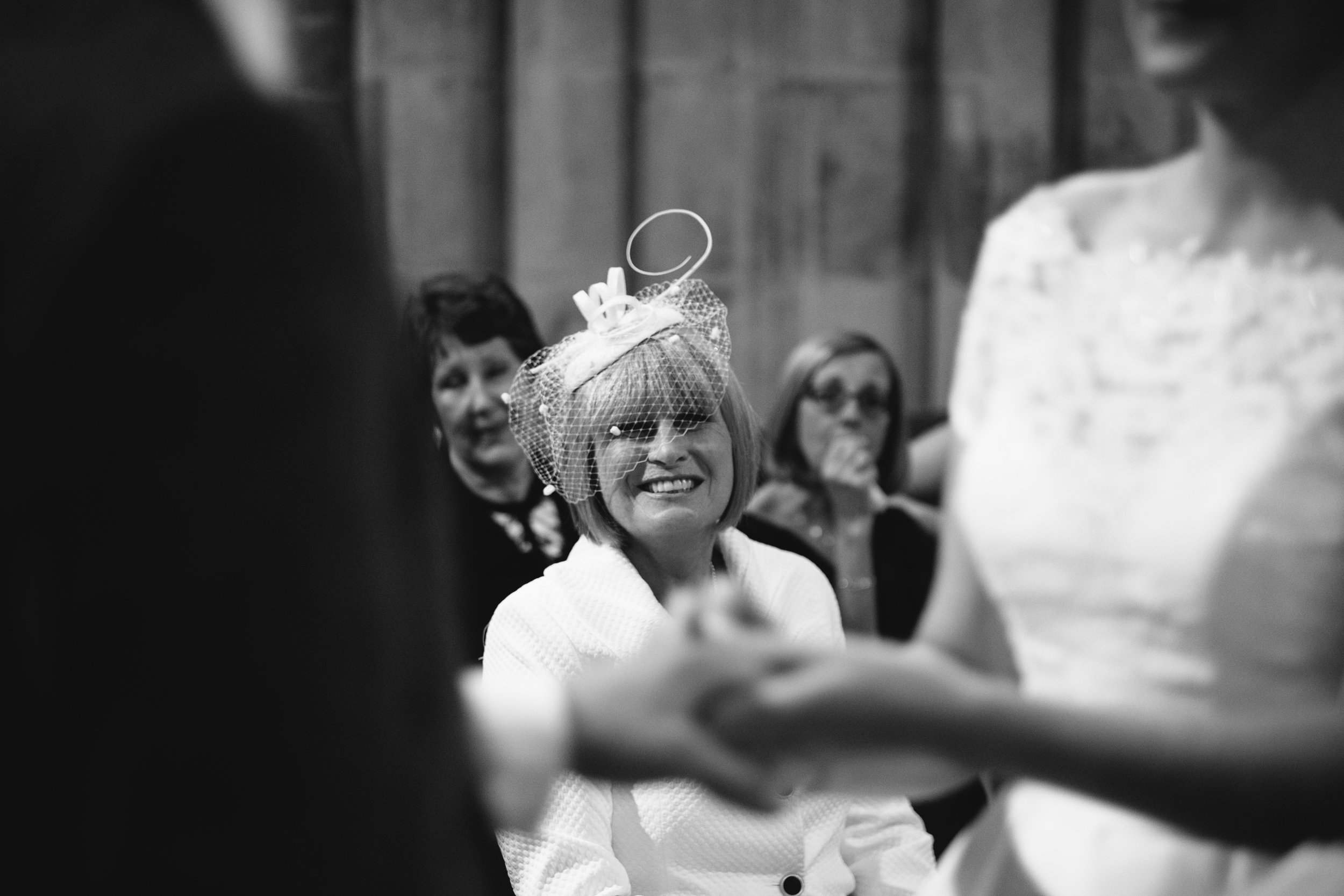 Black and white photo of the mother of the bride looks on as the bride and groom hold hands during their wedding ceremony
