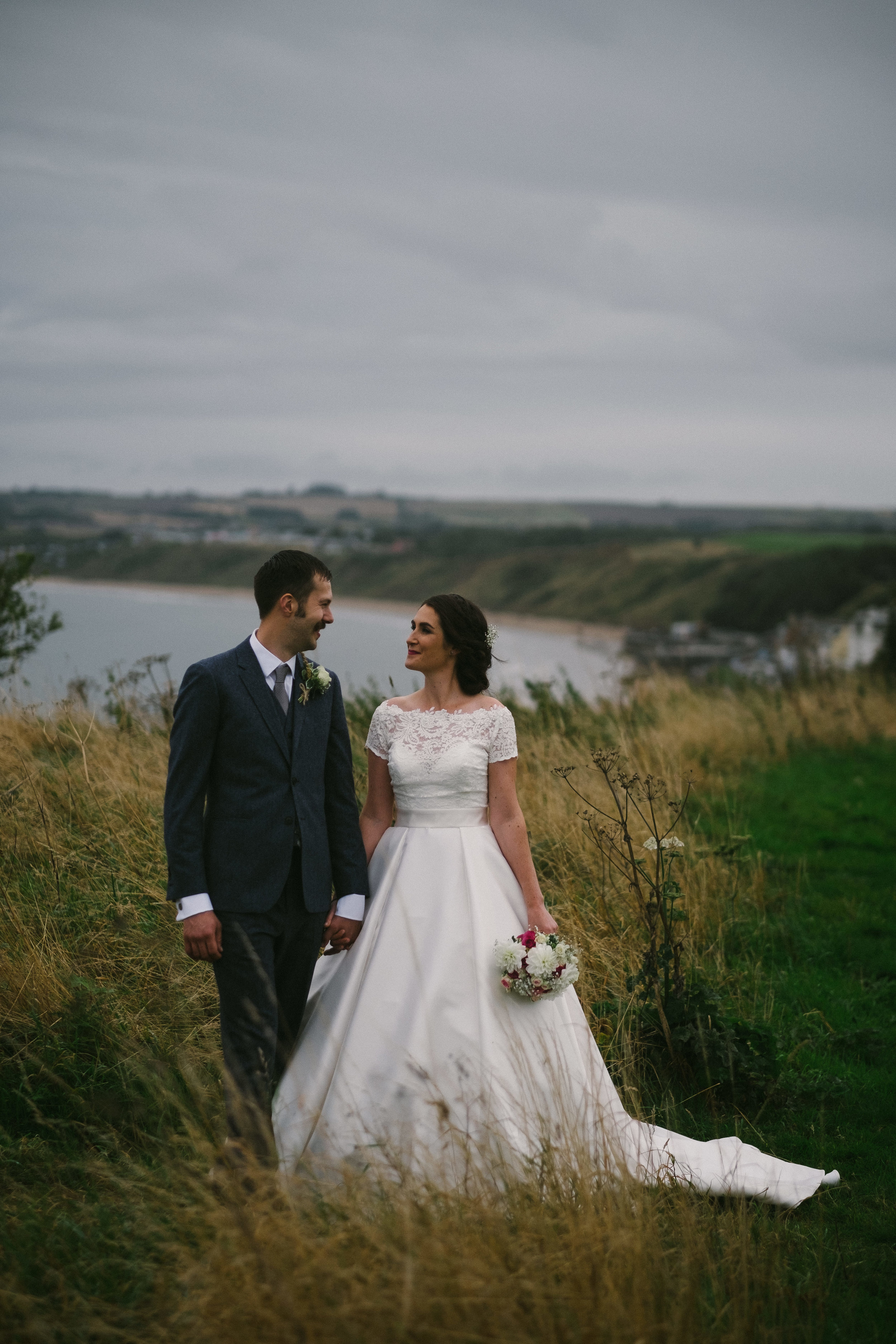 Bride and groom look into each others eyes while standing on the clifftops on the Yorkshire coast