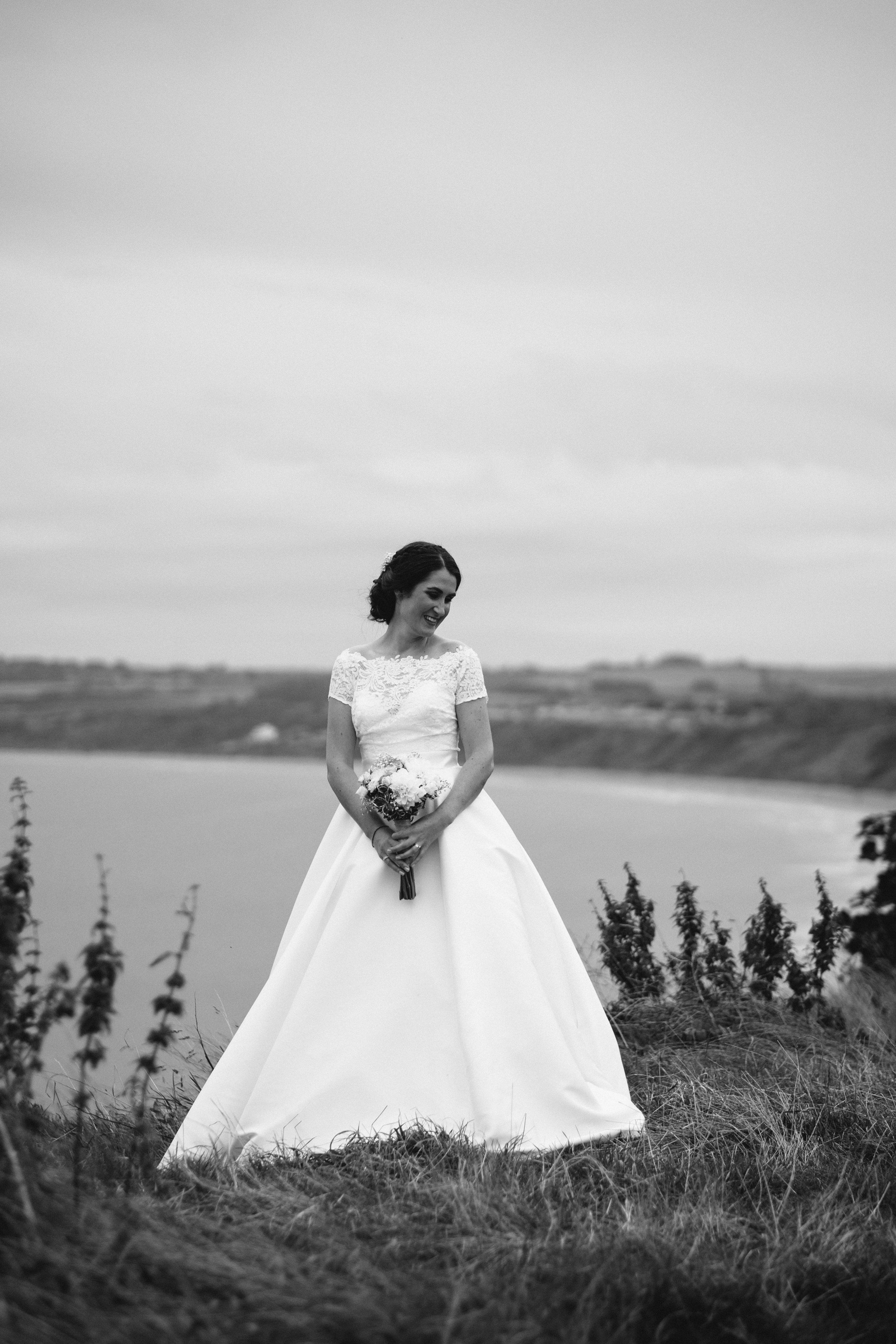 Black and white photo of the bride standing on the cliffs above the Yorkshire coast