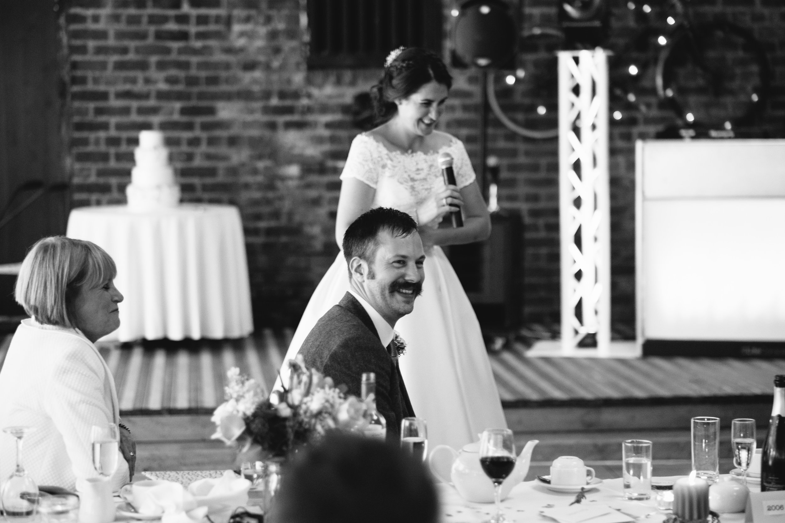 Black and white photo of the groom laughing at the bride's speech