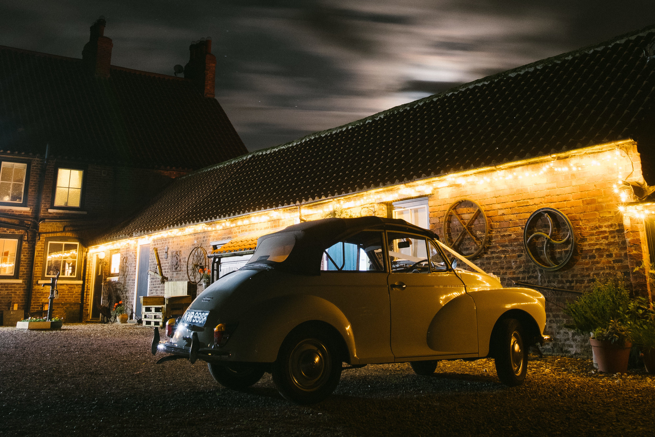 Brides car illuminated by golden lights at night on Dale Farm