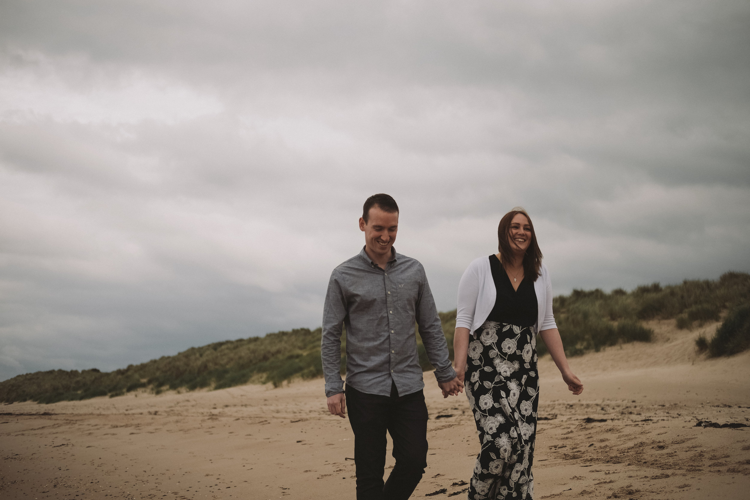 Couple stroll hand in hand along the beach on the Northumberland coast
