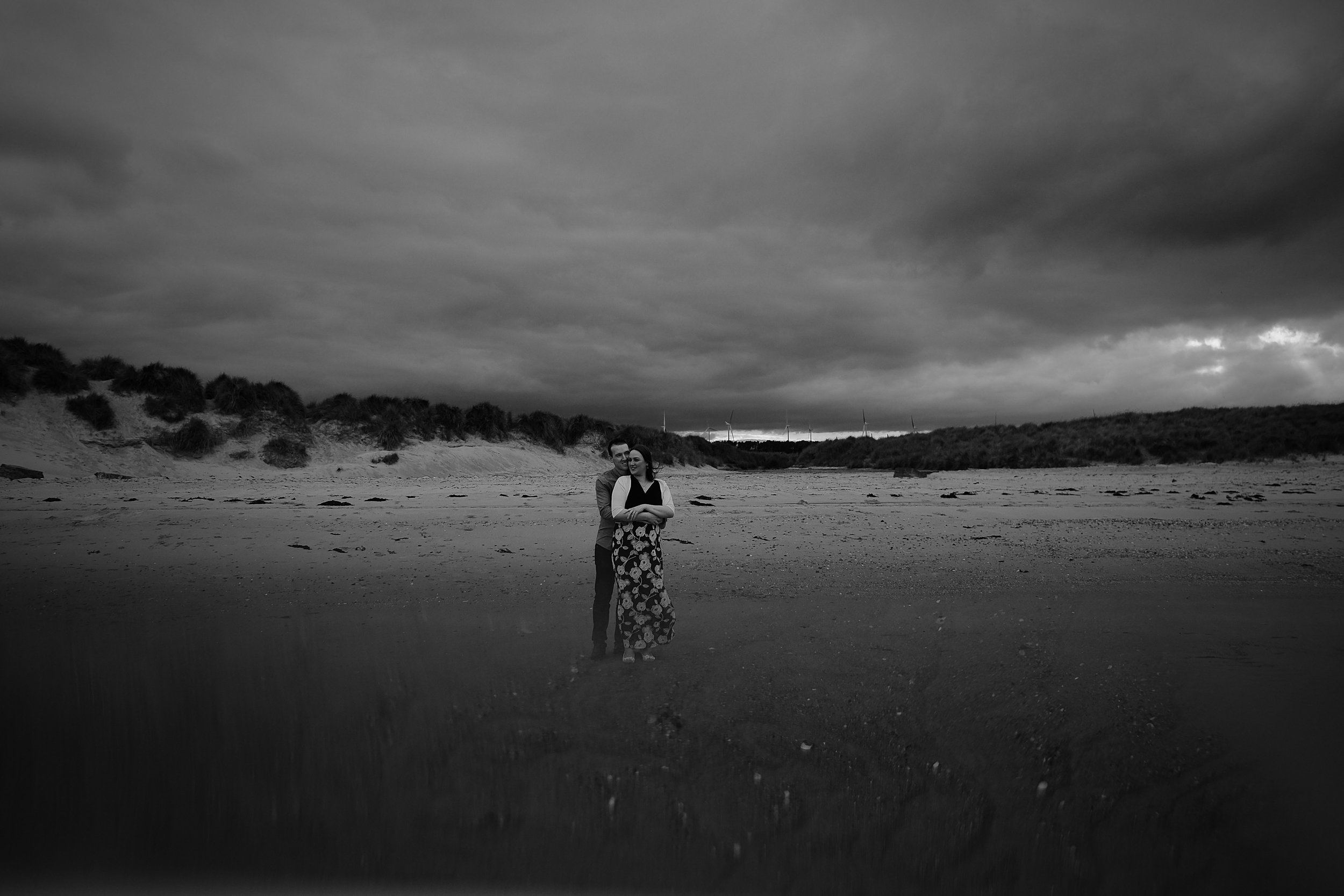 Black and white photo of couple cuddling on beach as storm clouds move in