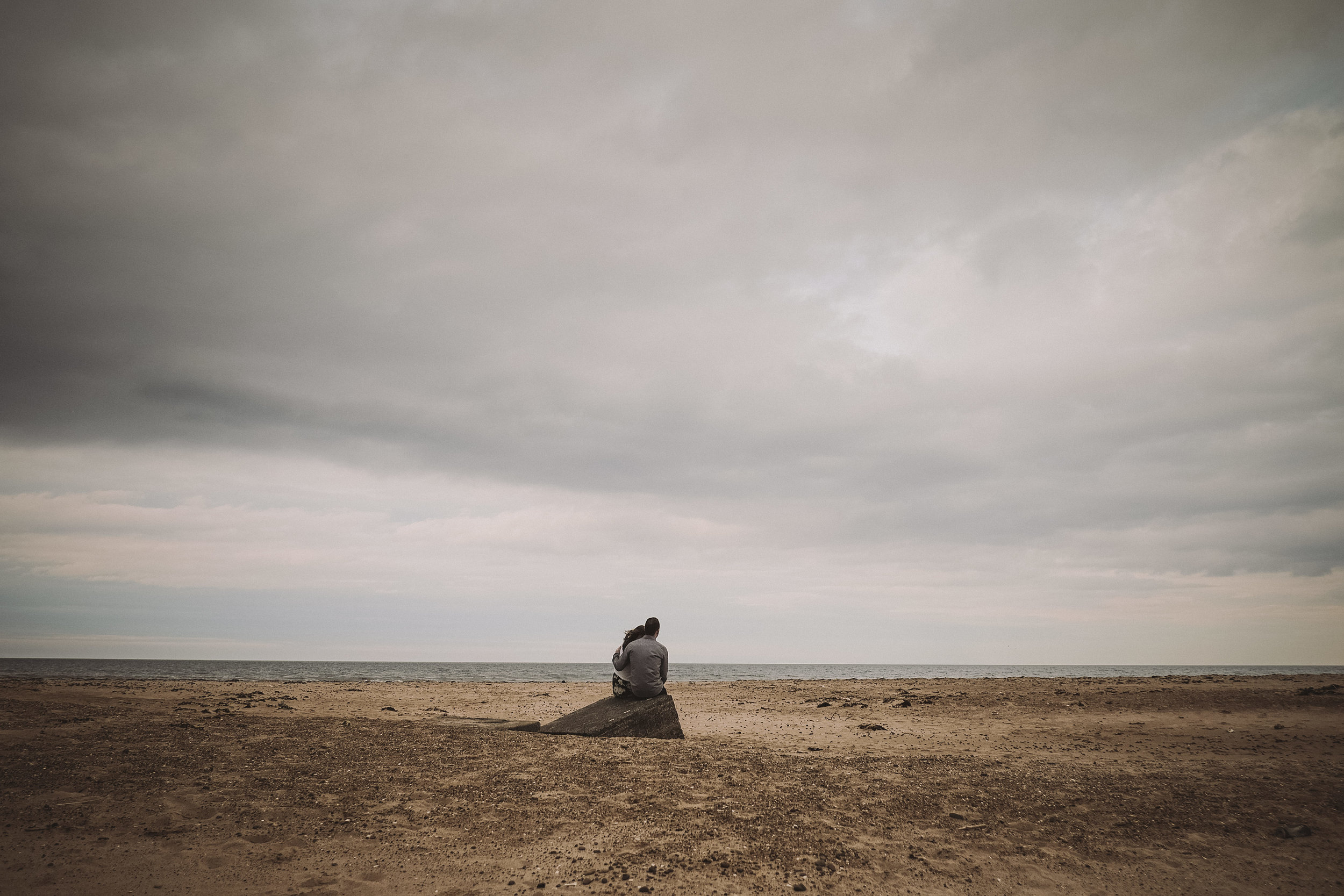 Couple sit on tank trap on engagement session at Druridge Bay Northumberland
