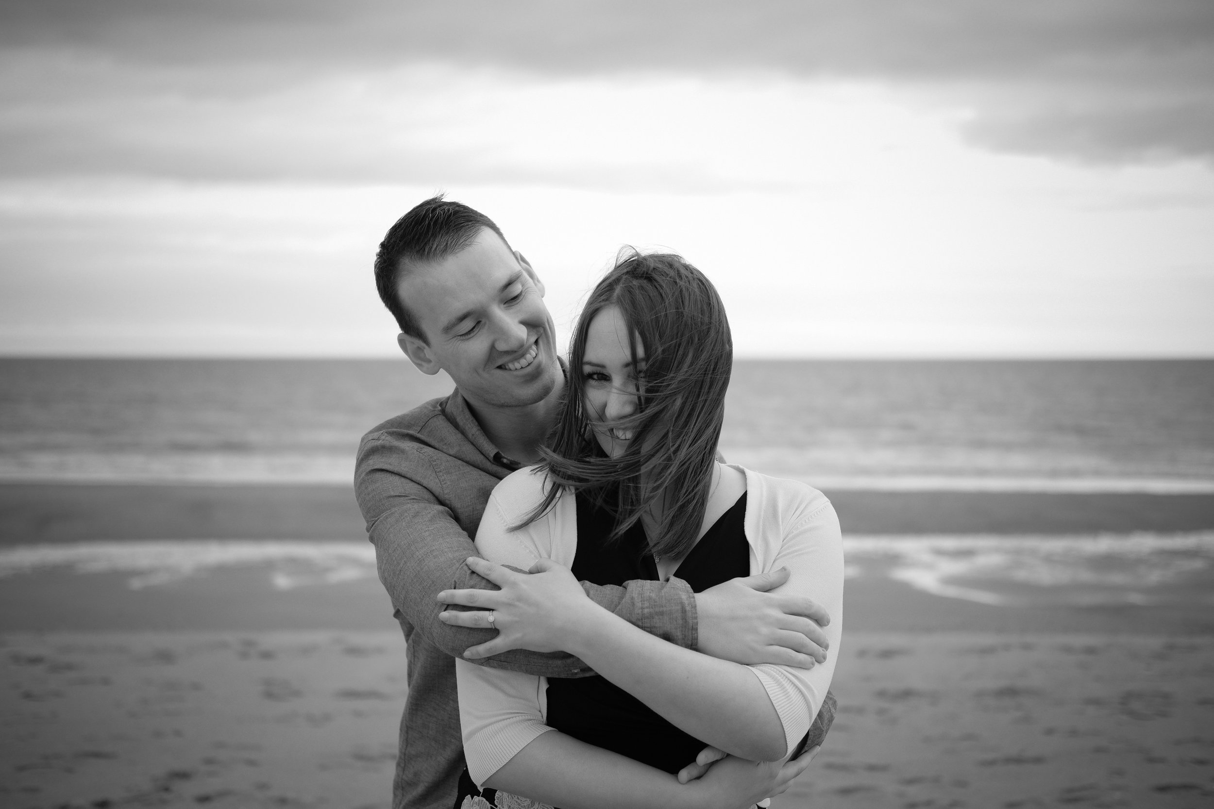 Black and white photo of couple cuddling tight while the wind catches girls hair