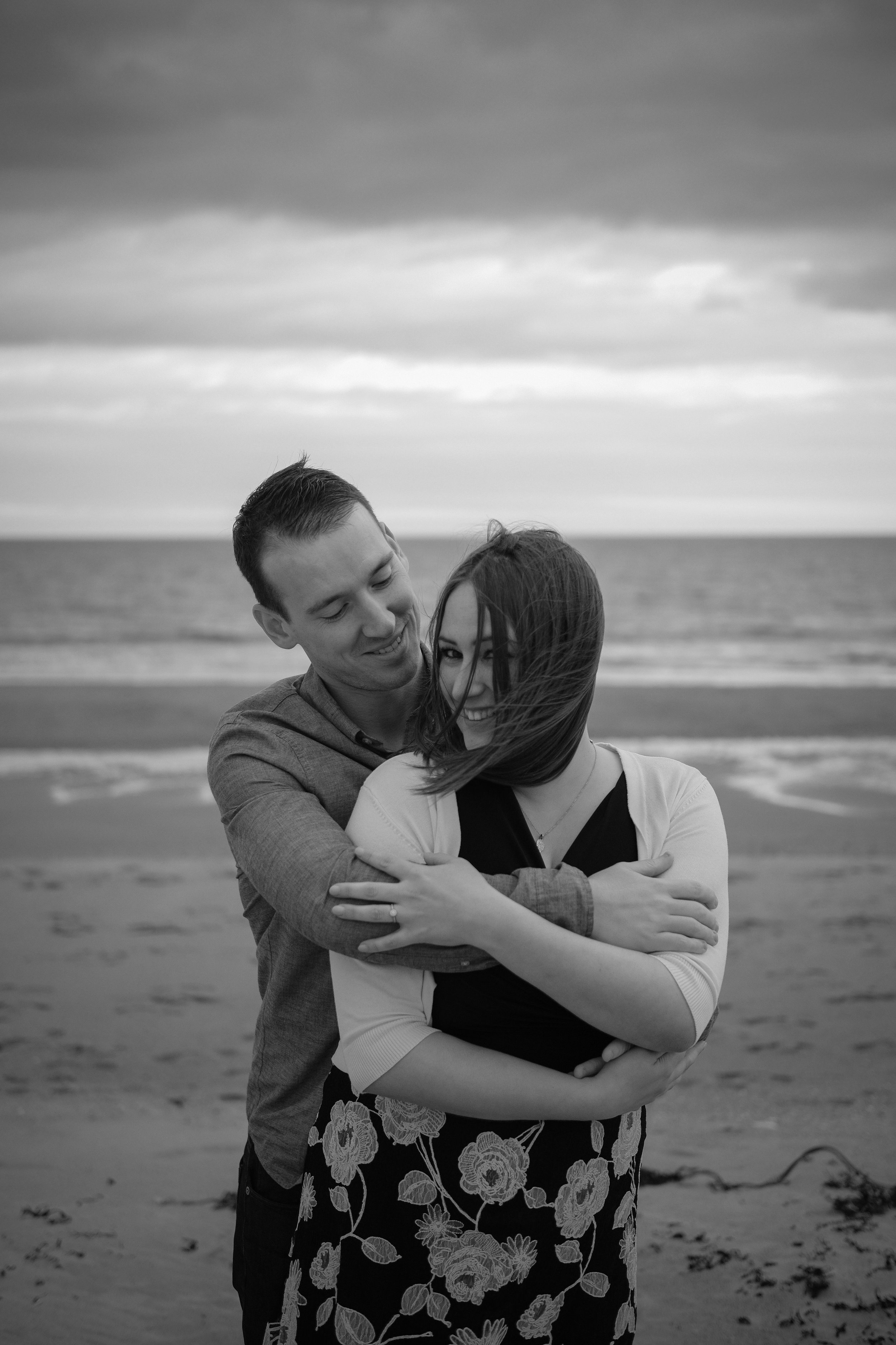 Black and white photo of couple cuddling on beach while girl looks at camera