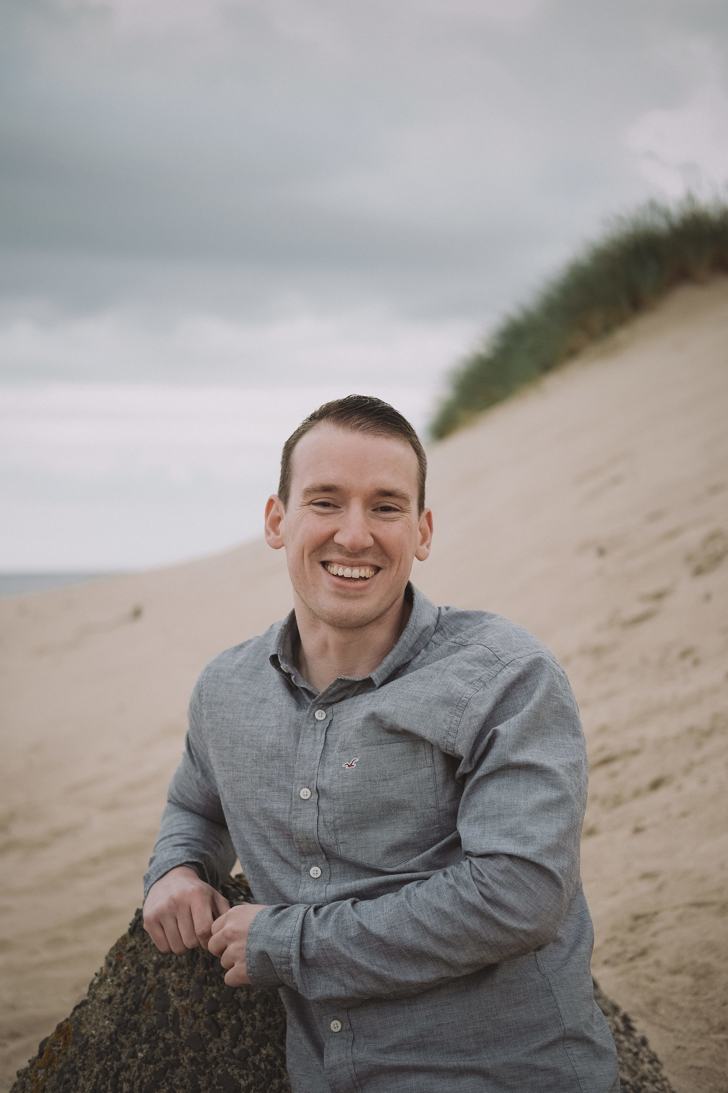 Groom to be smiles at camera while leaning back on engagement session at Druridge Bay, Northumberland