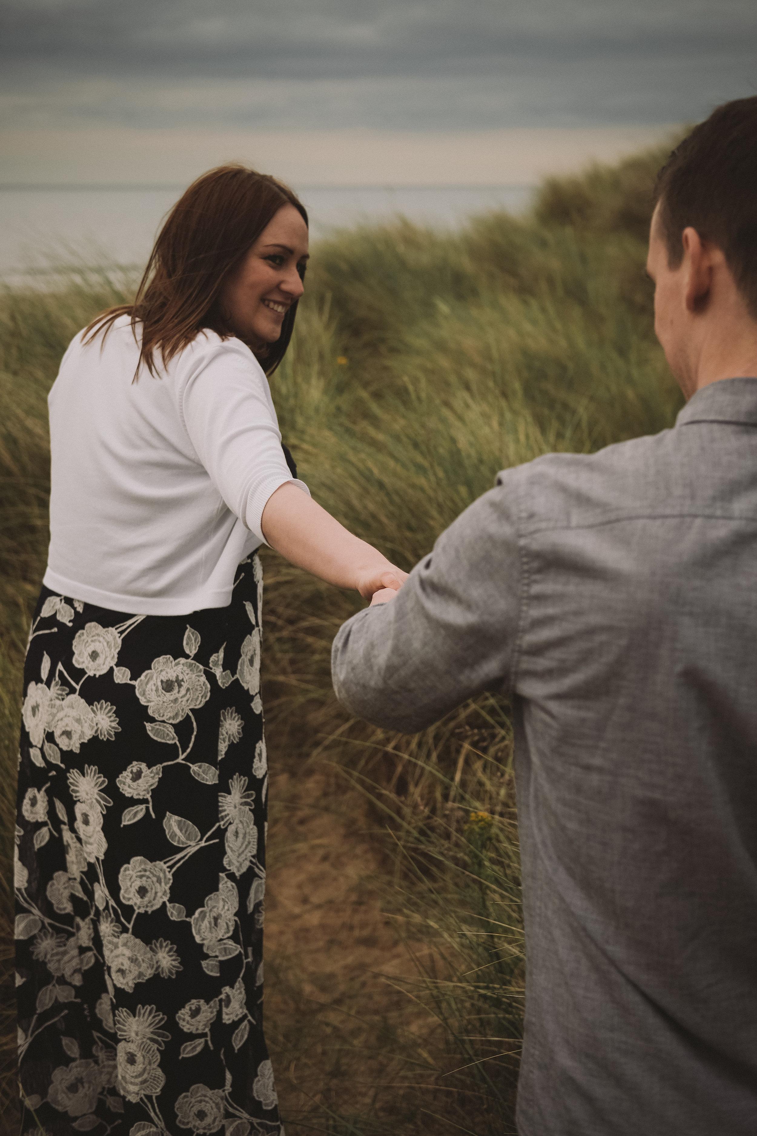 Girl leads guy through sand dunes on pre-wedding photoshoot on Northumberland coast