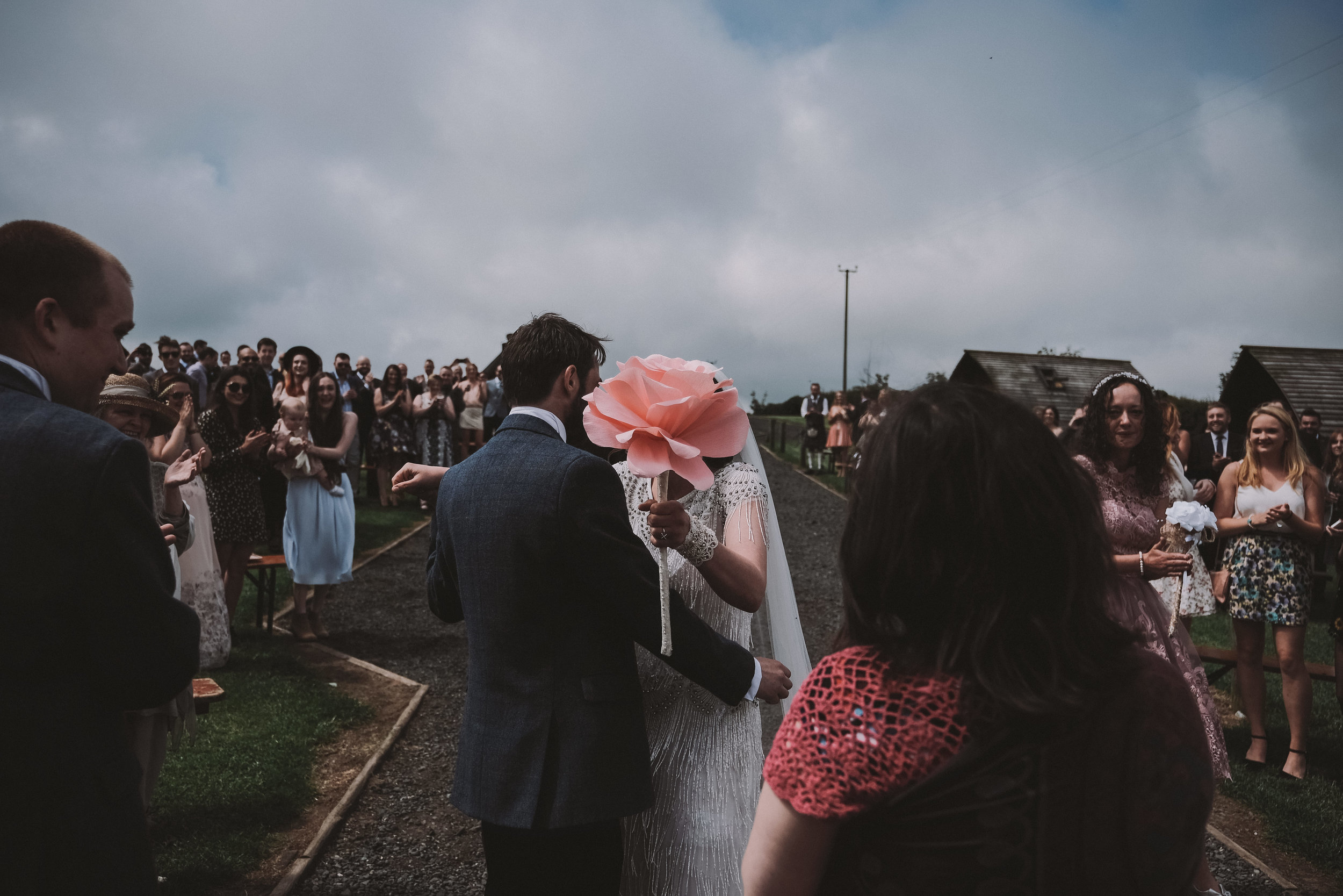 The bride and groom kiss at the start of their wedding ceremony obscured by the bride's giant flower