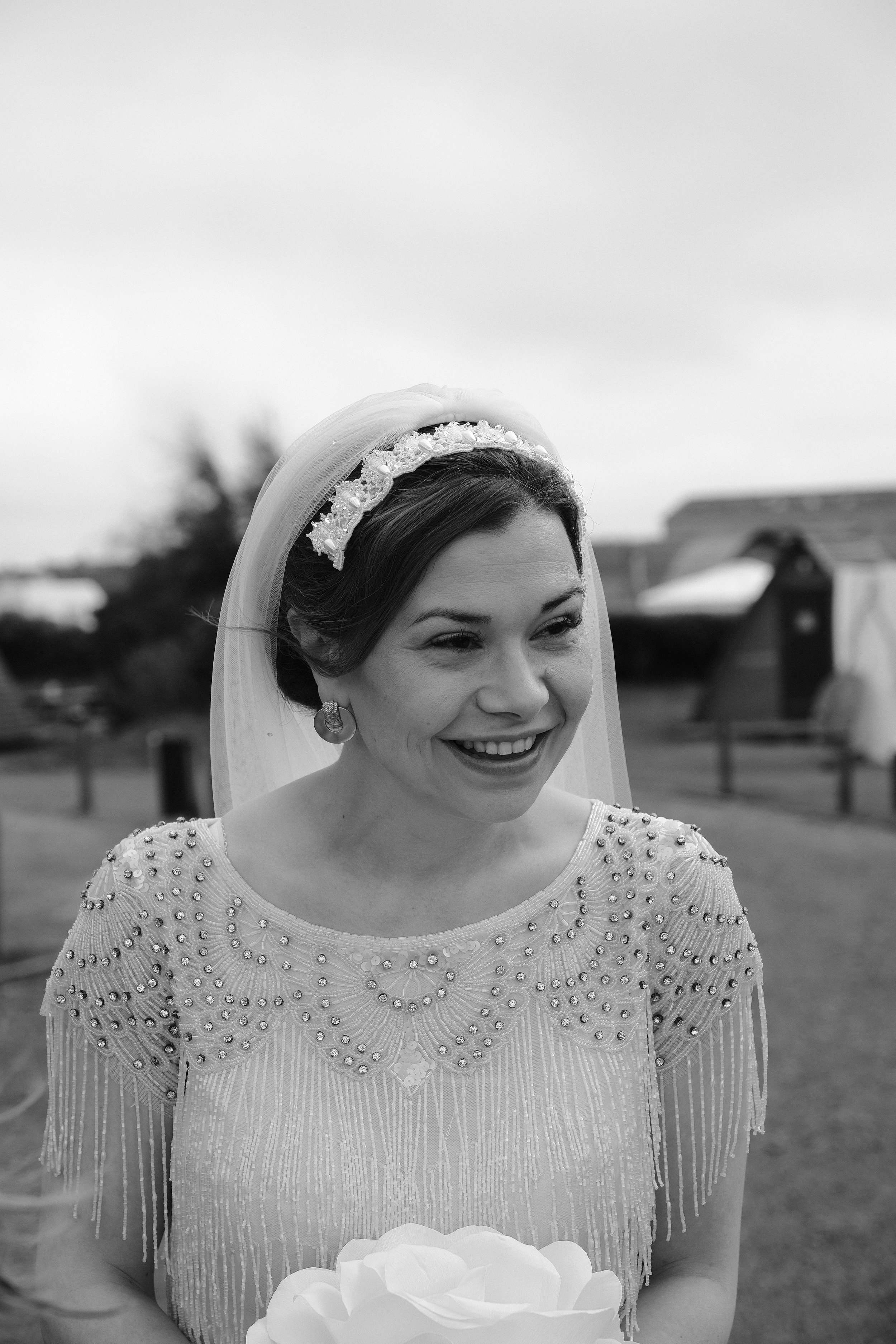 Black and white photo of the bride smiling just before her wedding ceremony