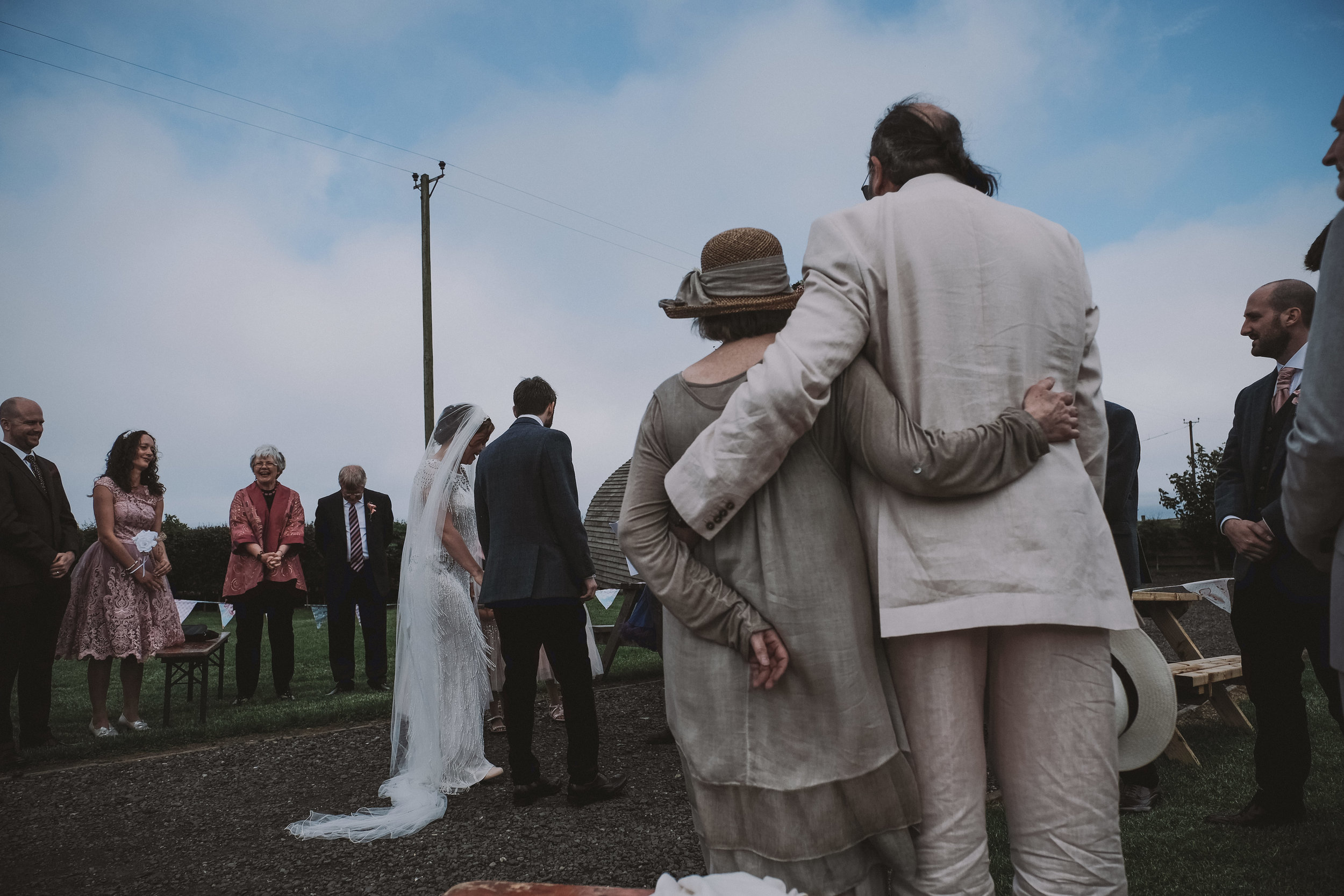 Bride and groom hold hands during the wedding ceremony while their parents cuddle