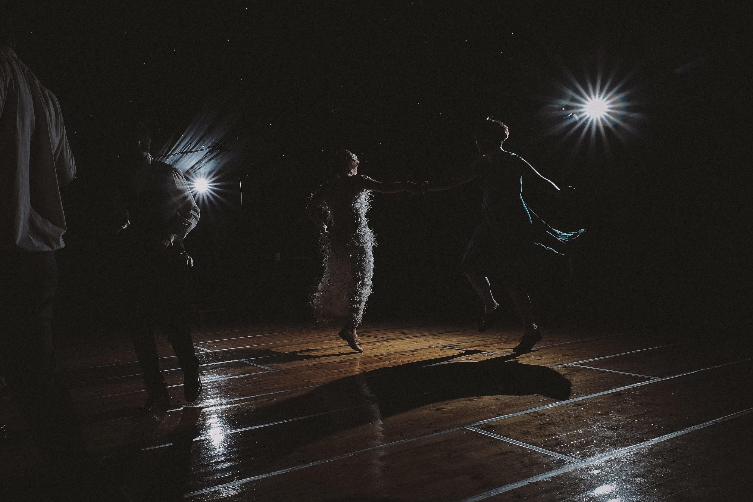 Bride and bridesmaid dance vigorously in dramatic light