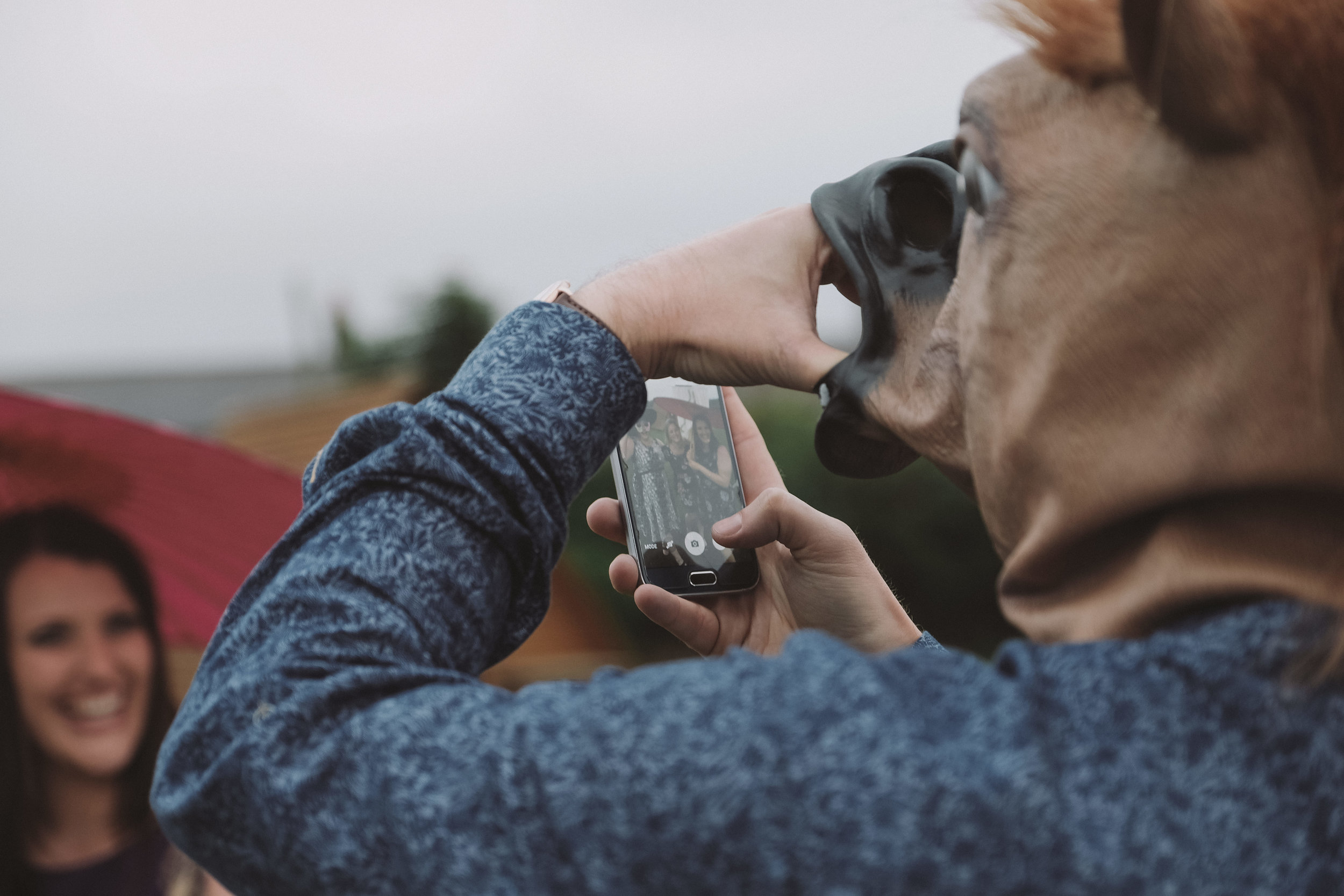 Wedding guest wearing a horse mask takes a photo