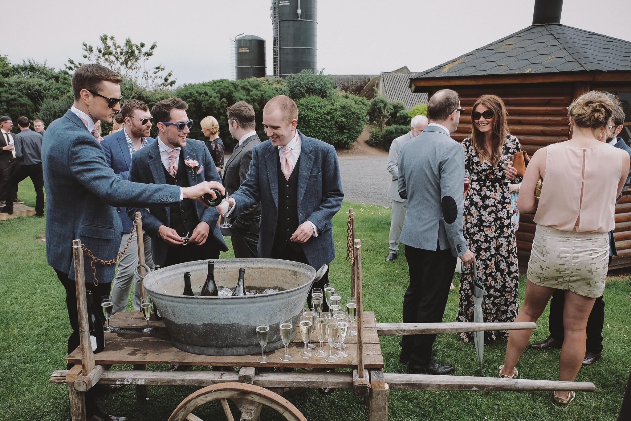 Groomsmen get beer from giant bucket at an outdoor wedding ceremony