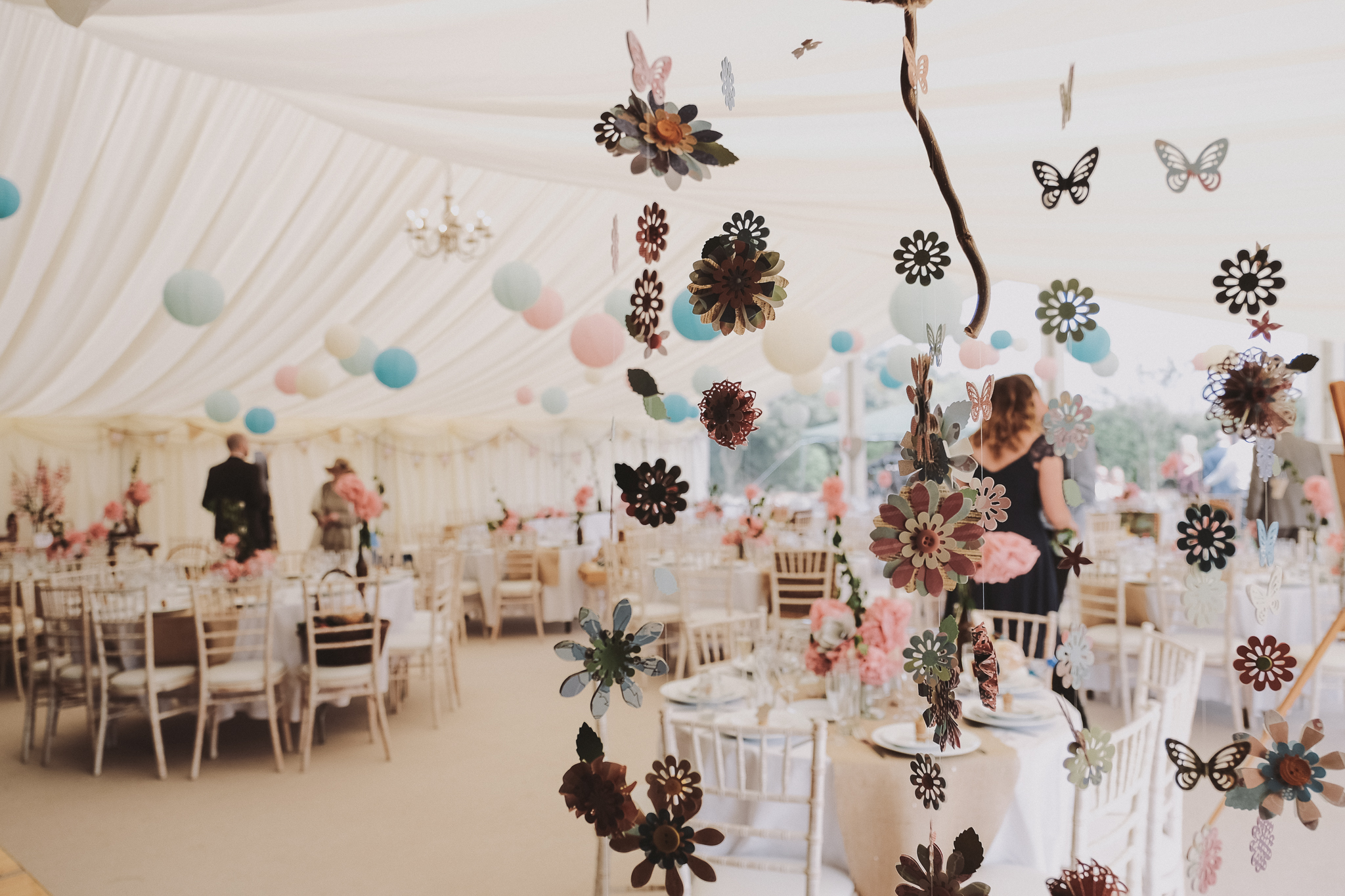 Paper decorations hang in in a wedding marquee
