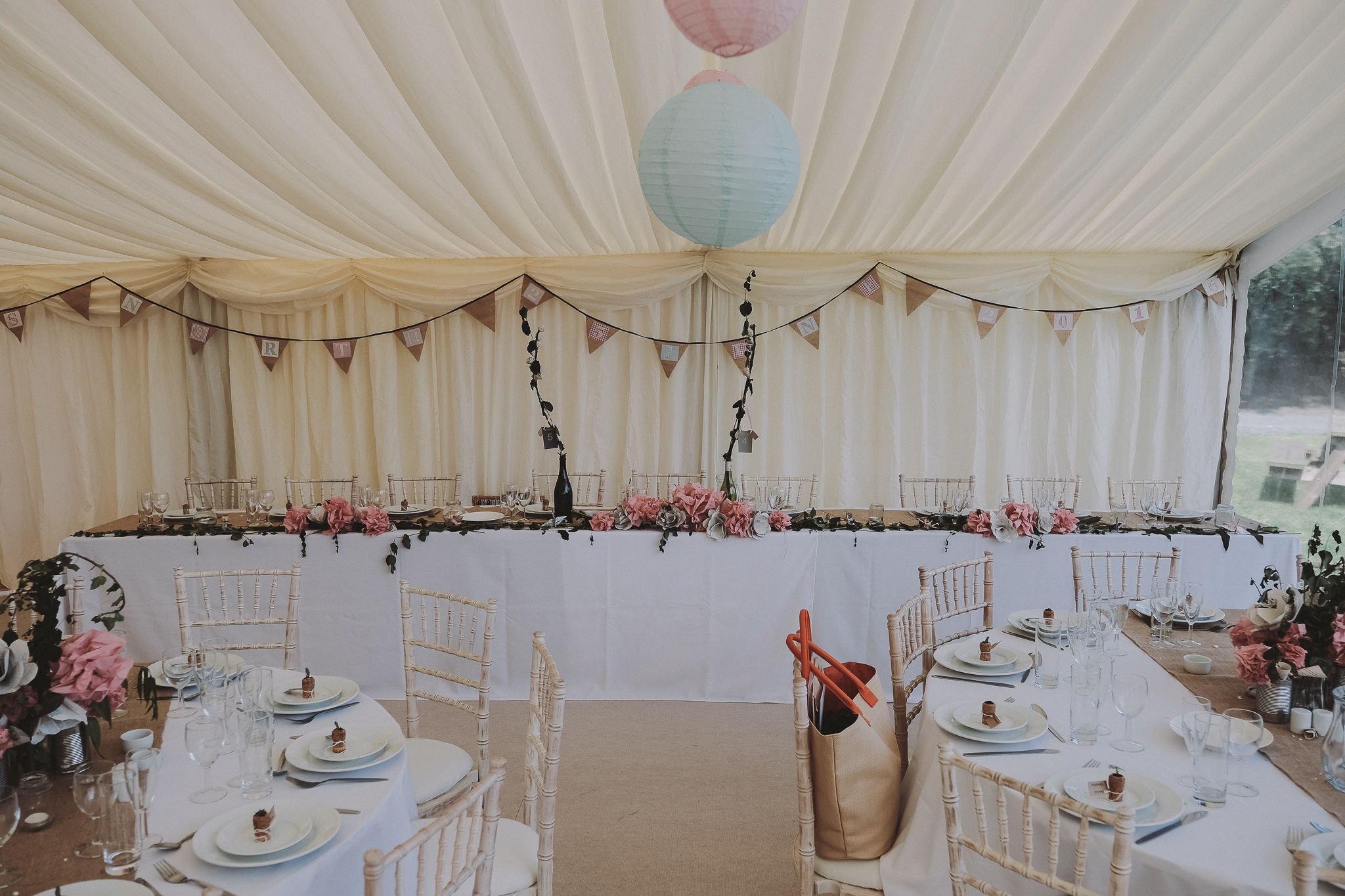 The top table in a marquee showing a long line of homemade paper flowers