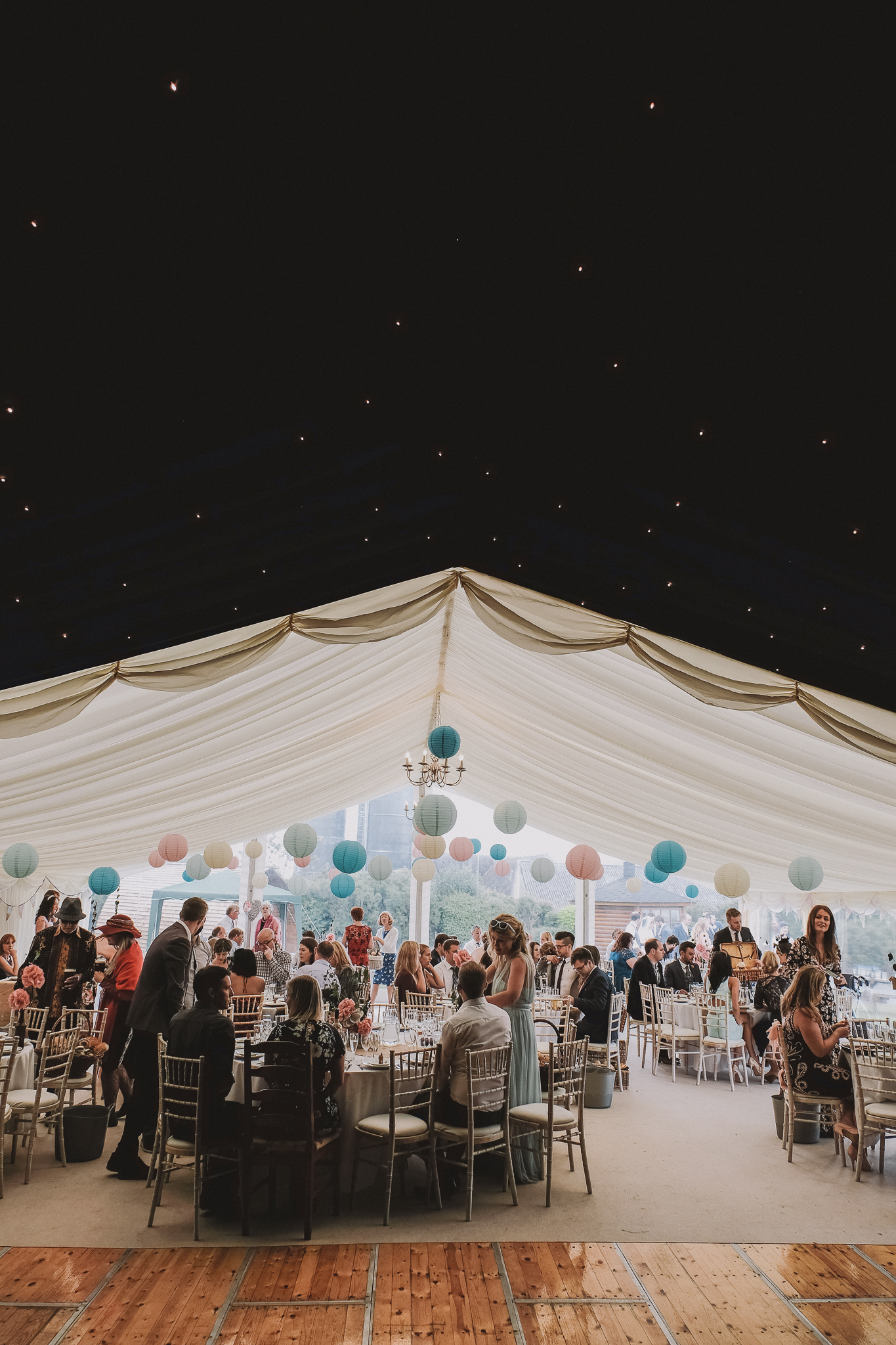 Dramatic photo of wedding guests sitting in marquee with twinkling lights in the darkness above them