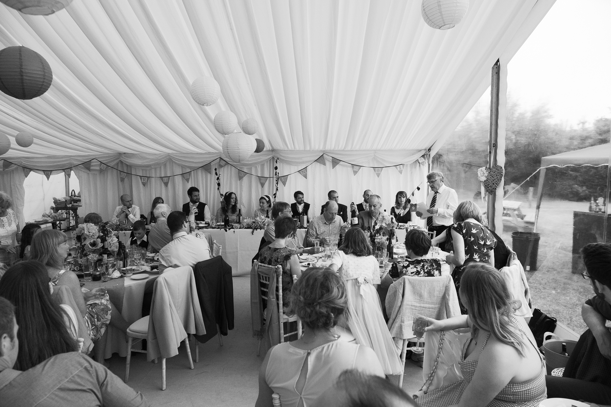 Black and white photo of wedding guests in marquee at Potadoodledoo