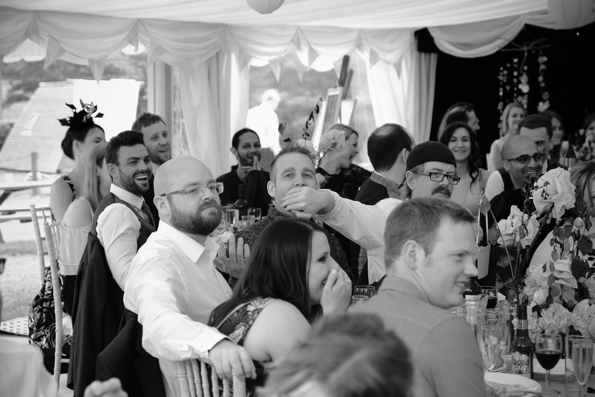 Black and white photo of one groomsman holding his hand over another groomsman's mouth