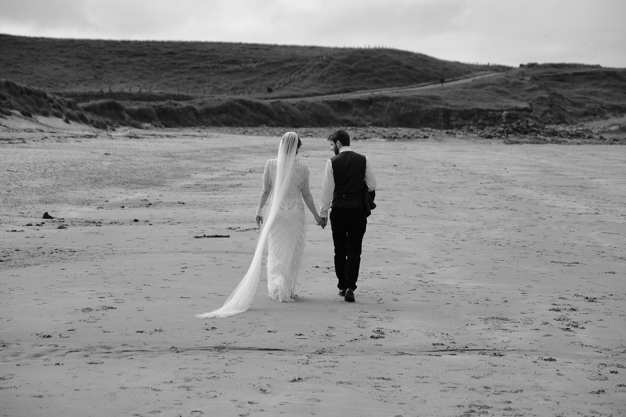 Black and white photo of bride and groom holding hands walking away from the camera on a beach