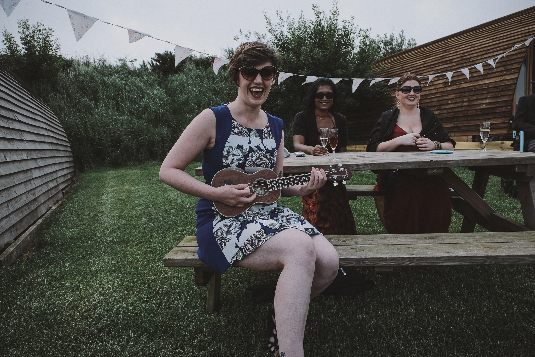 The brides entrance is accompanied by a sunglasses wearing ukulele player