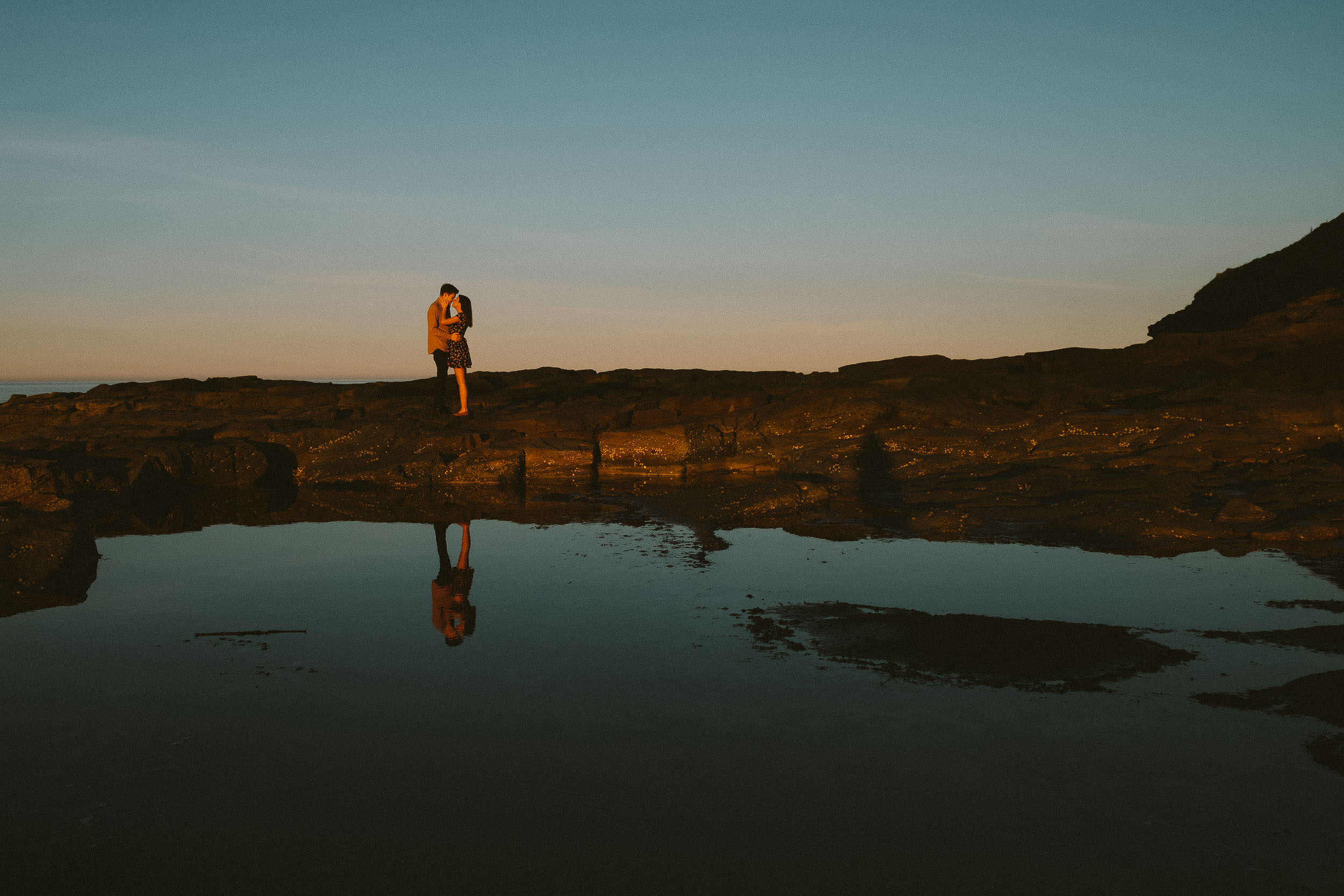 Serene photo of couple cuddling on rocks with reflection in water at sunset