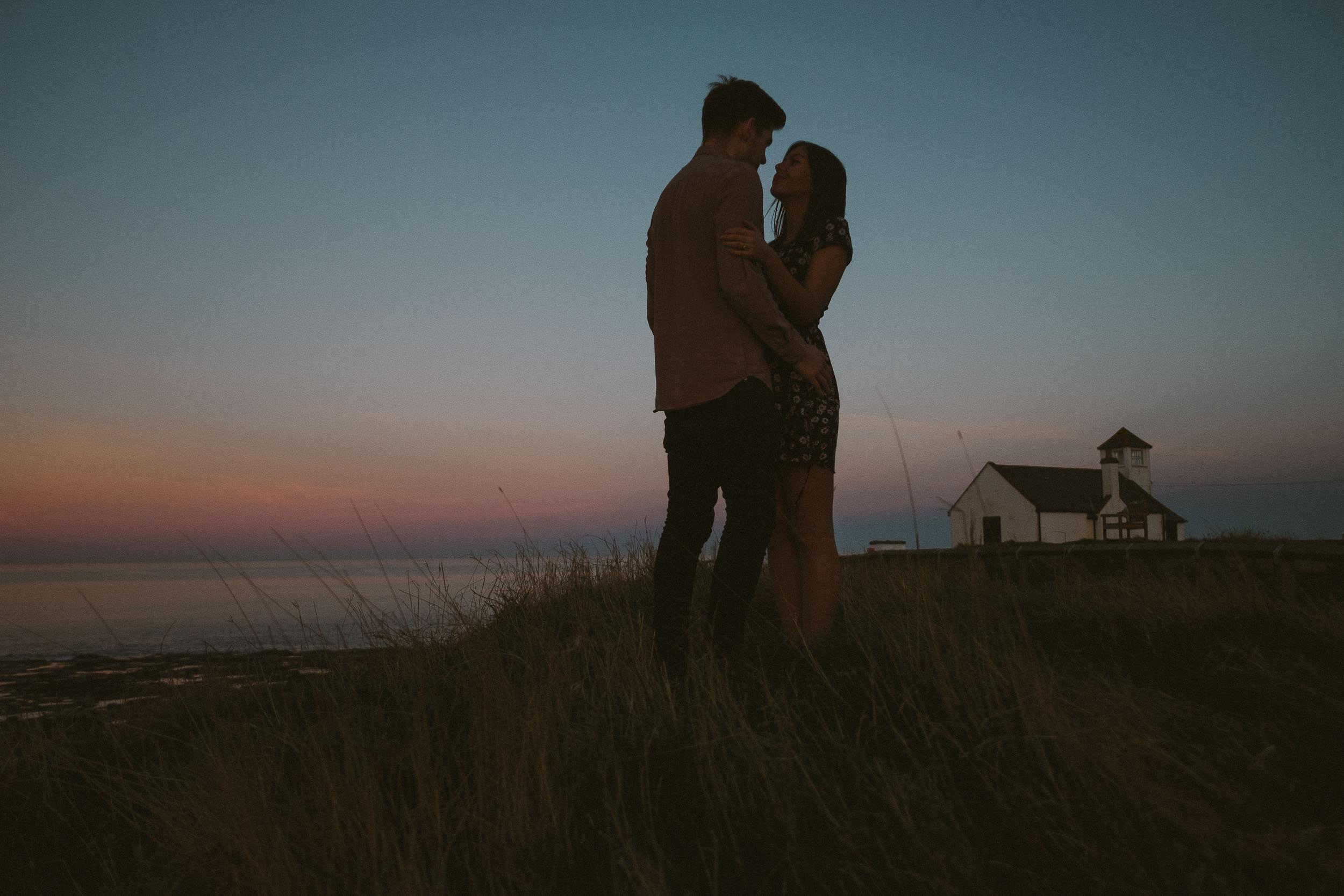 Couple embrace in beautiful sunset light at Seaton Sluice Northumberland