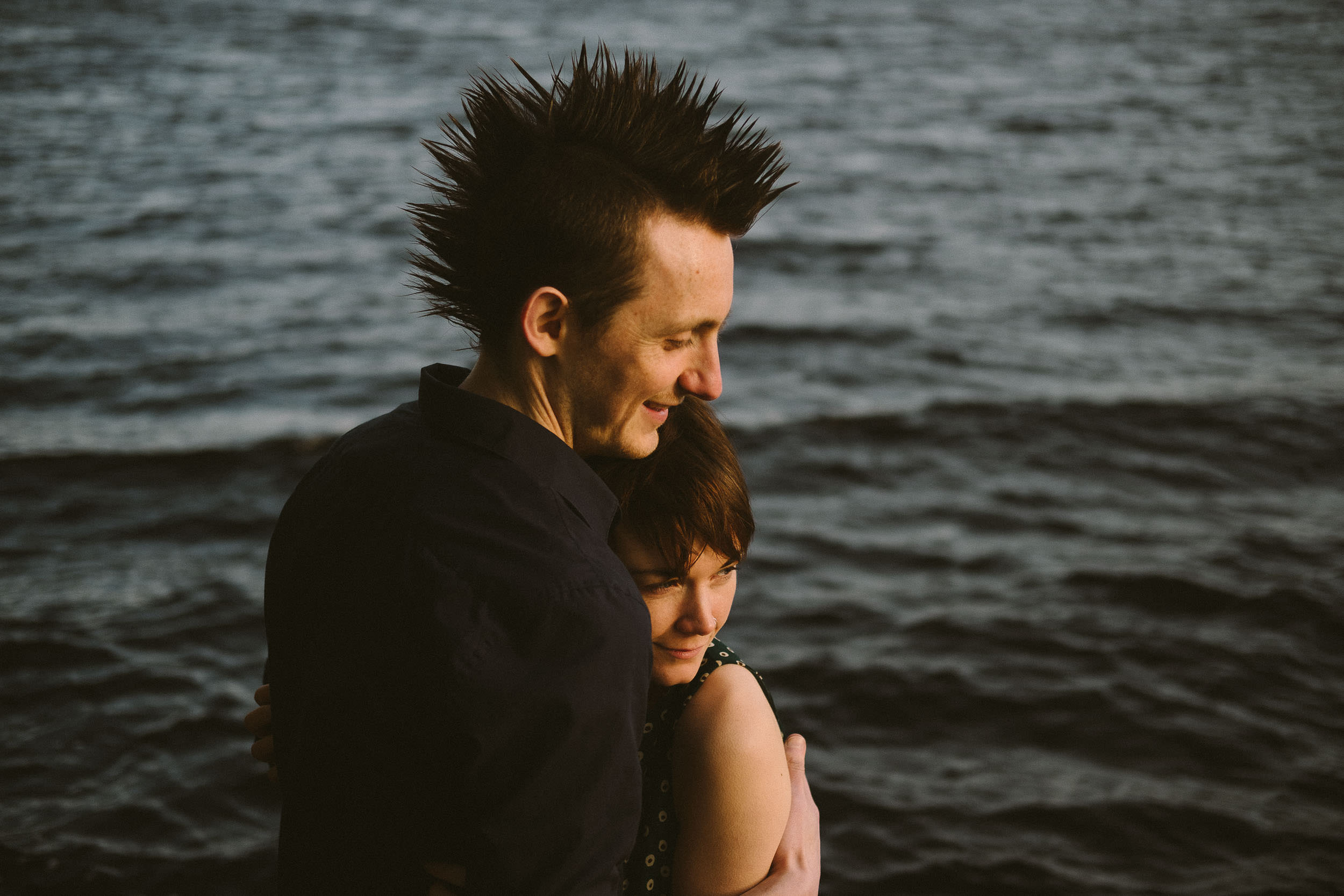 Punk couple with spiky hair cuddle with Kielder Water in the background