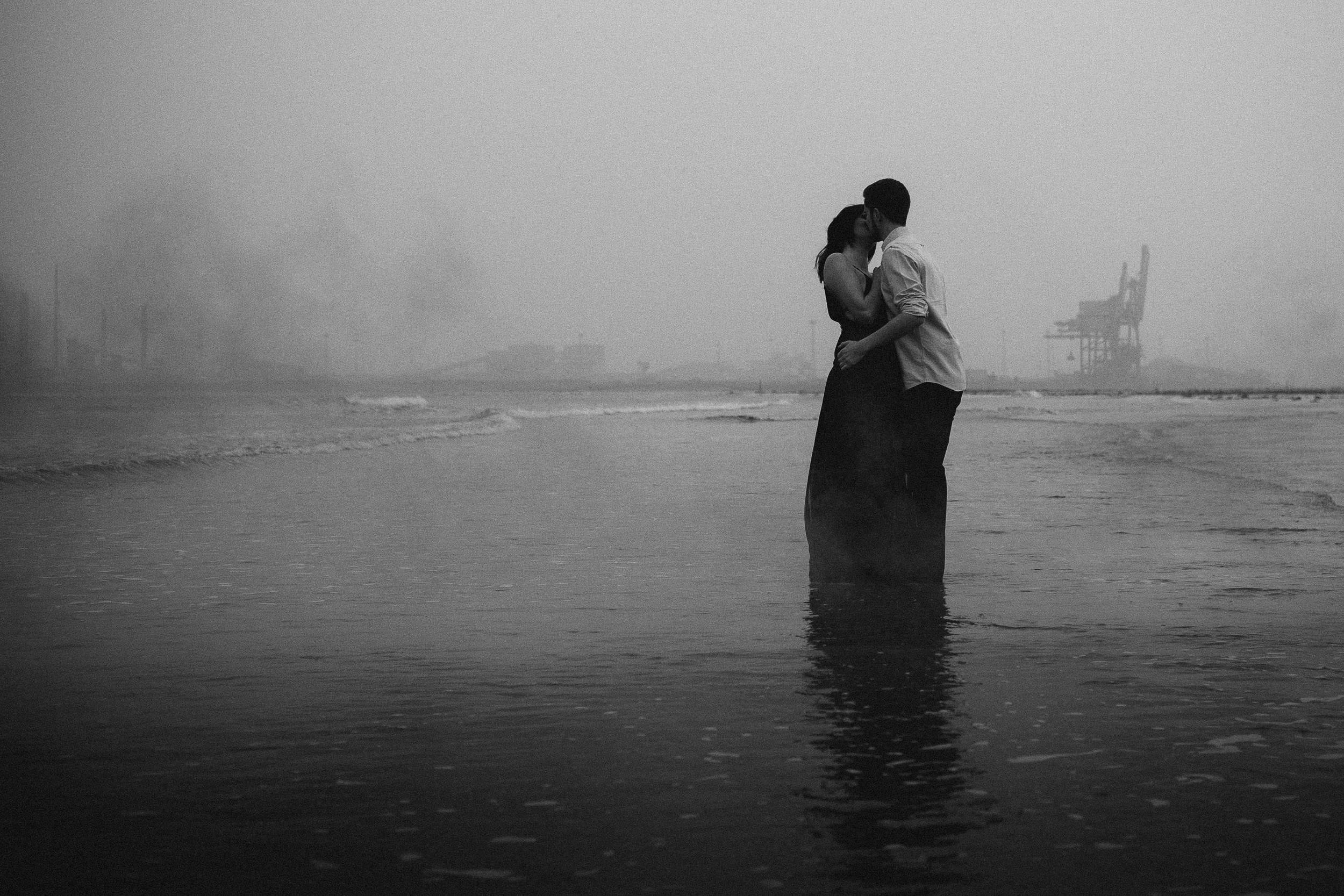 Couple embrace in a black and white photograph on an industrial beach with smoke and mist