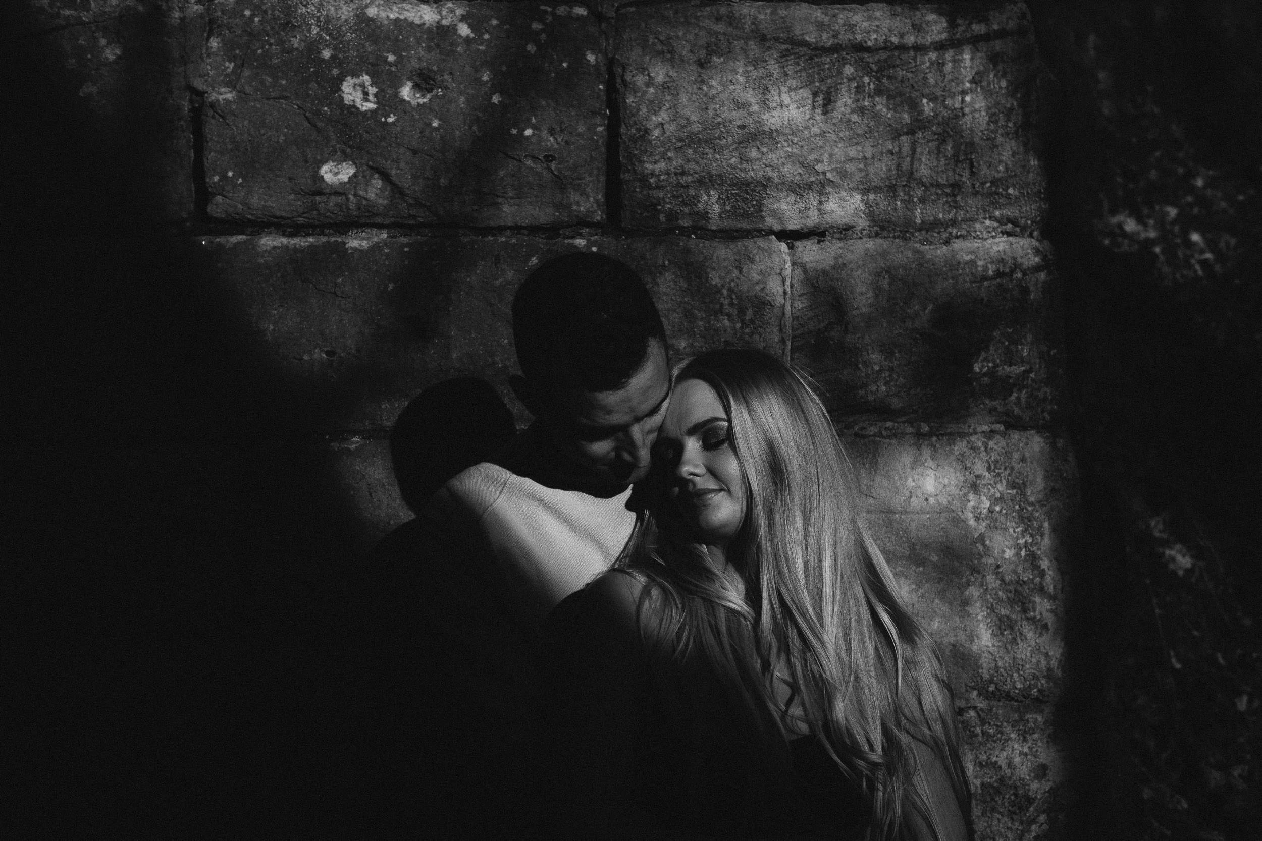 Moody black and white photo of couple leaning against rough wall in deep shadow