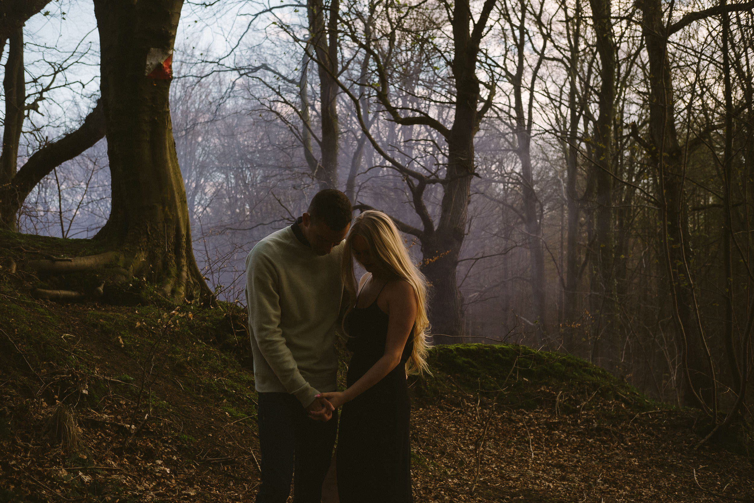 Couple hold hands while purple mist hangs in the air behind them in the forest