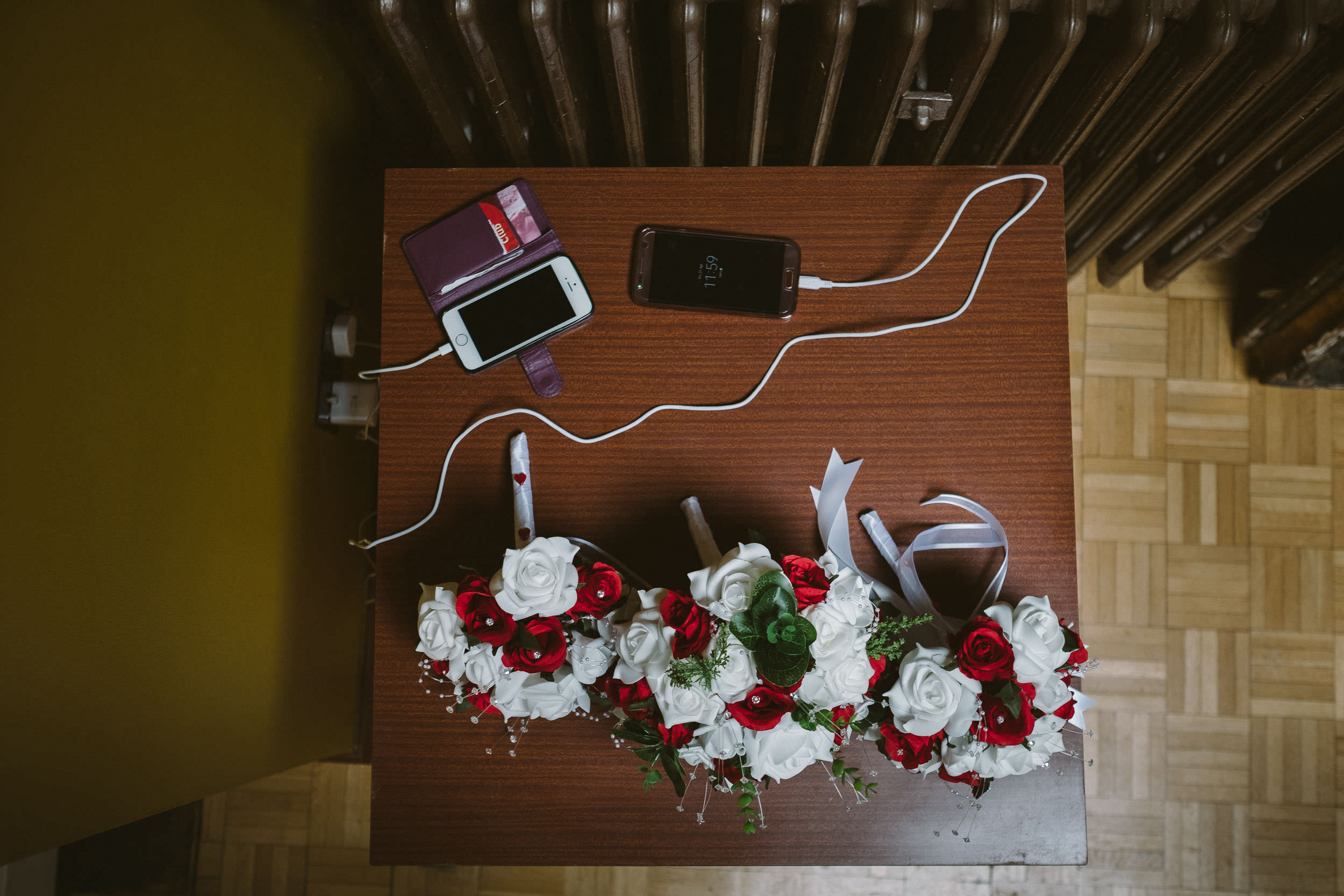 Wedding flowers lying on a table while telephones are charging