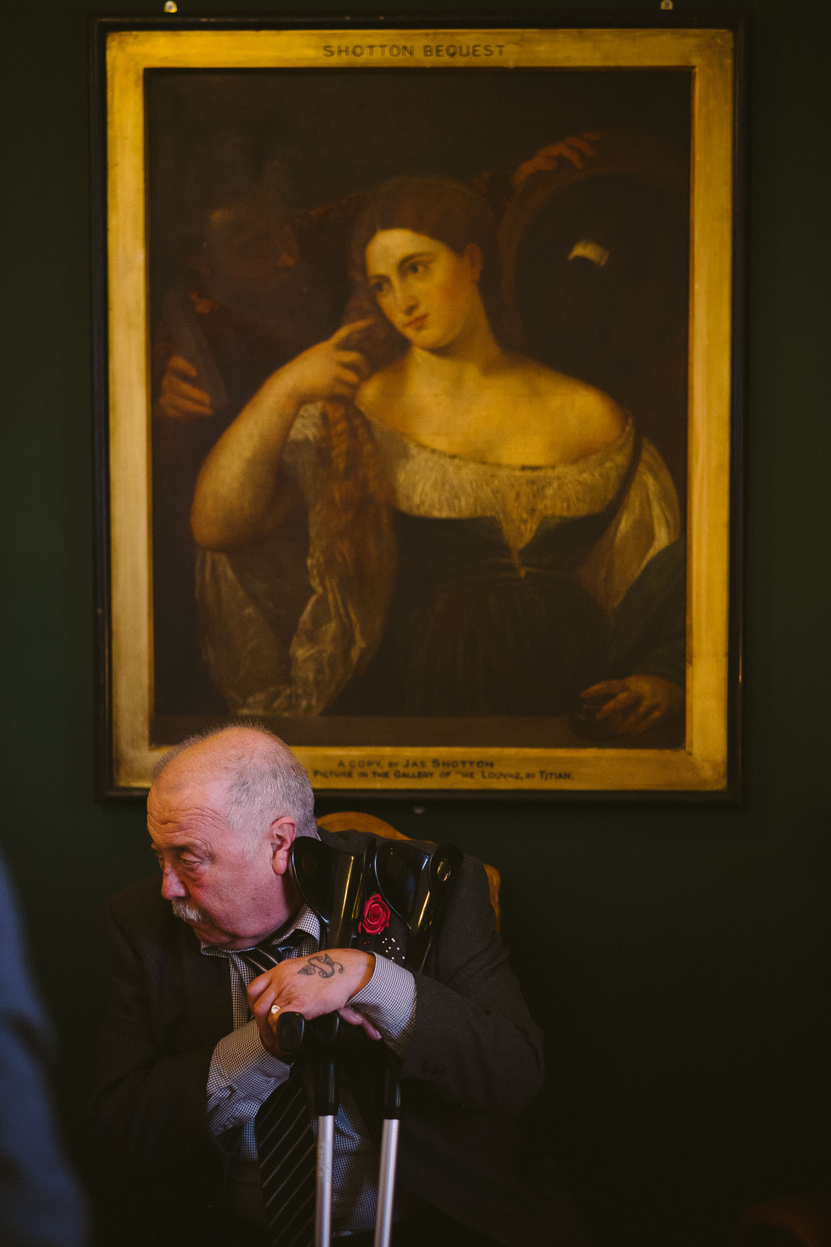 Wedding guest leans on his walking sticks with classical painting behind him at Wallsend Hall