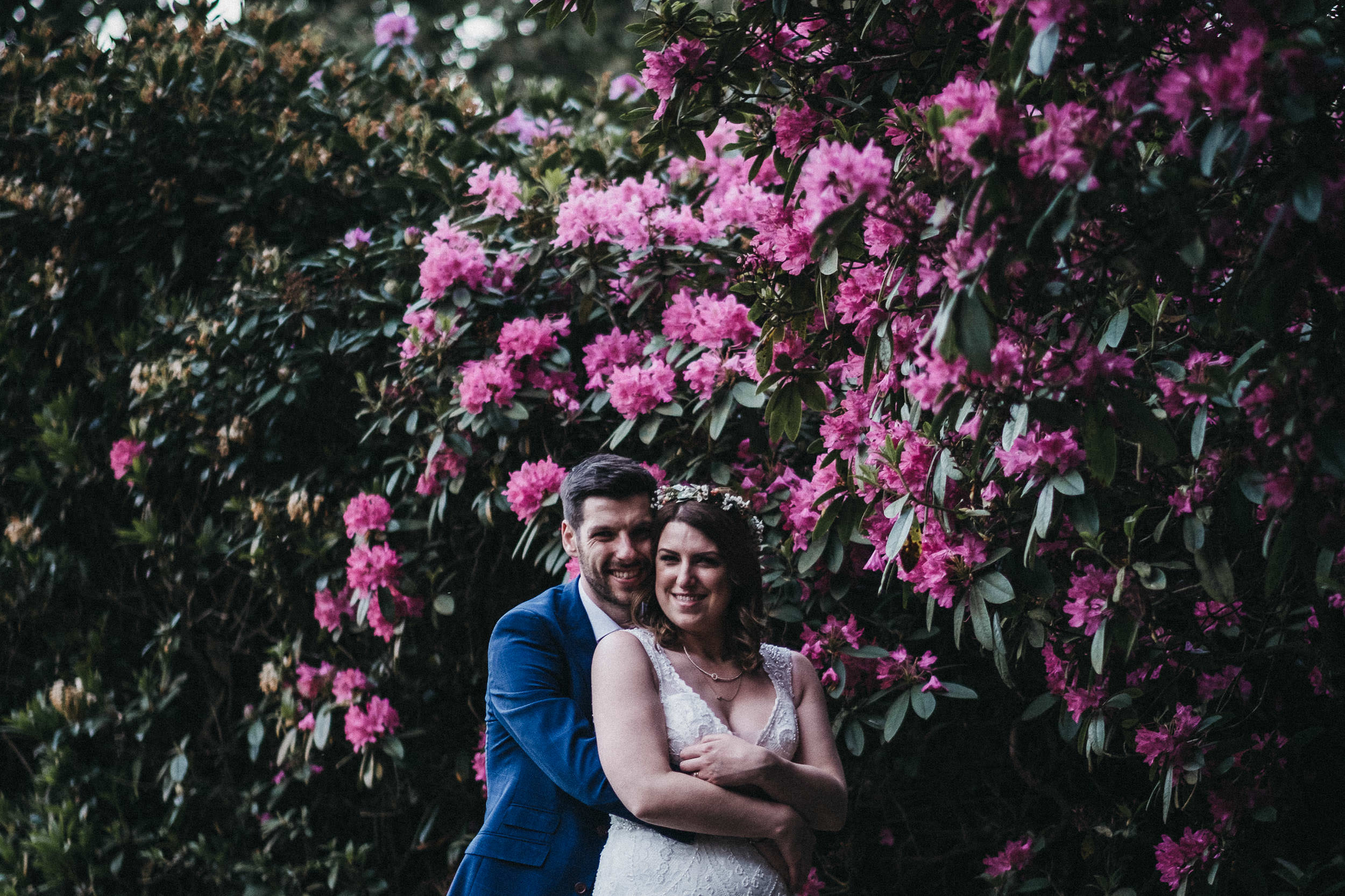 Bride and groom cuddle in front of a wall of pink flowers