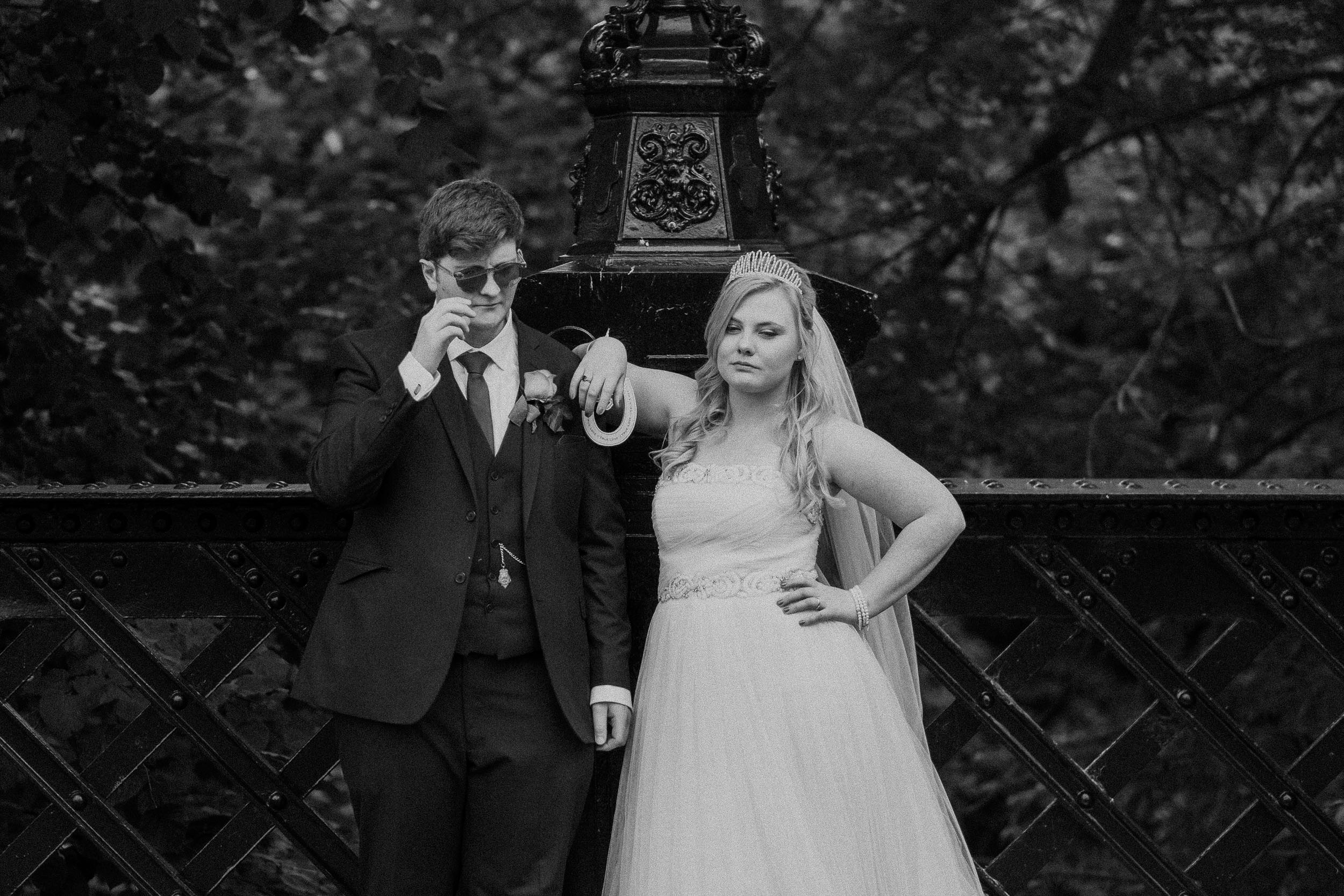 Cool black and white photo of bride and groom in sunglasses on bridge