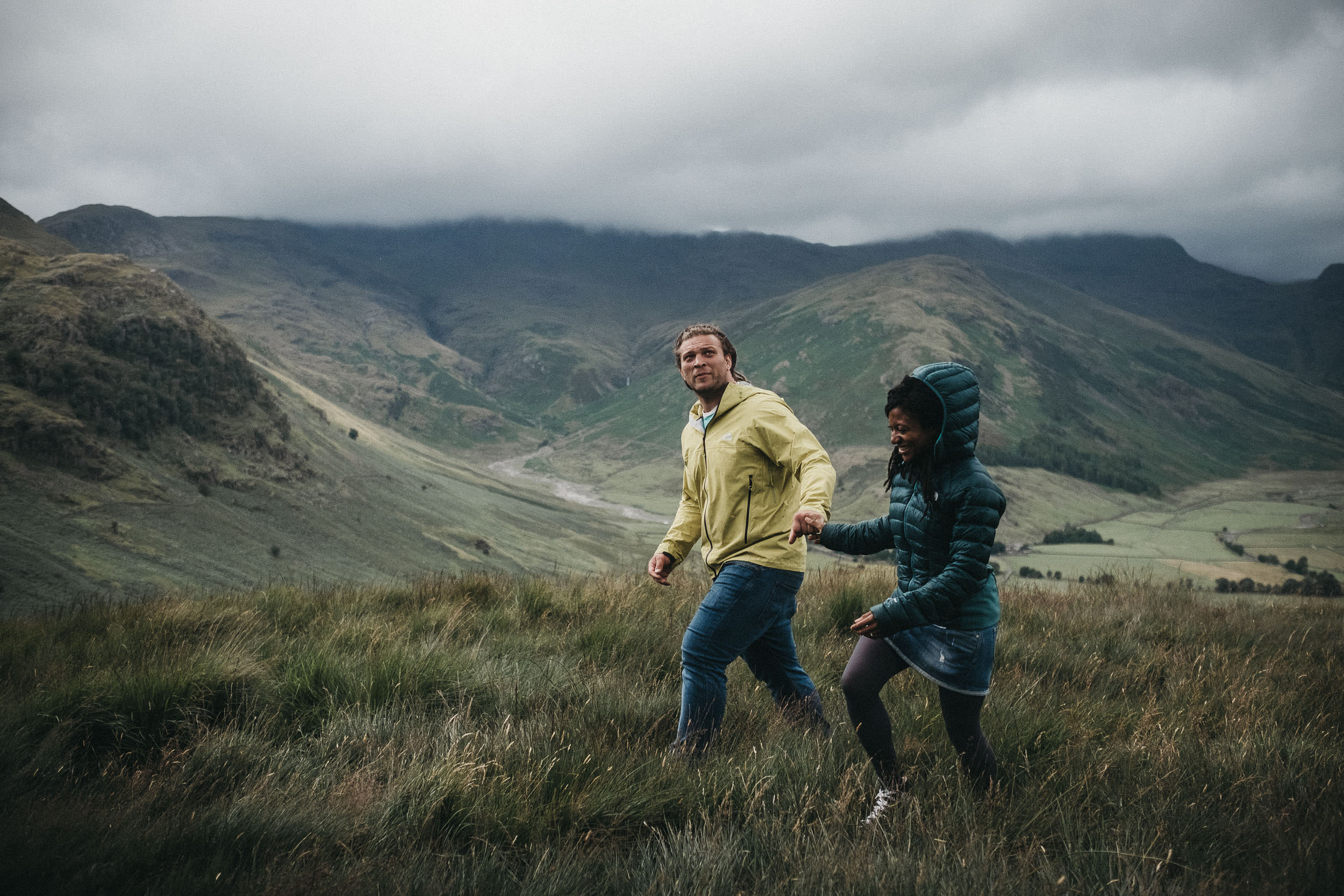 Couple walk over mountain in the Lake District in the rain