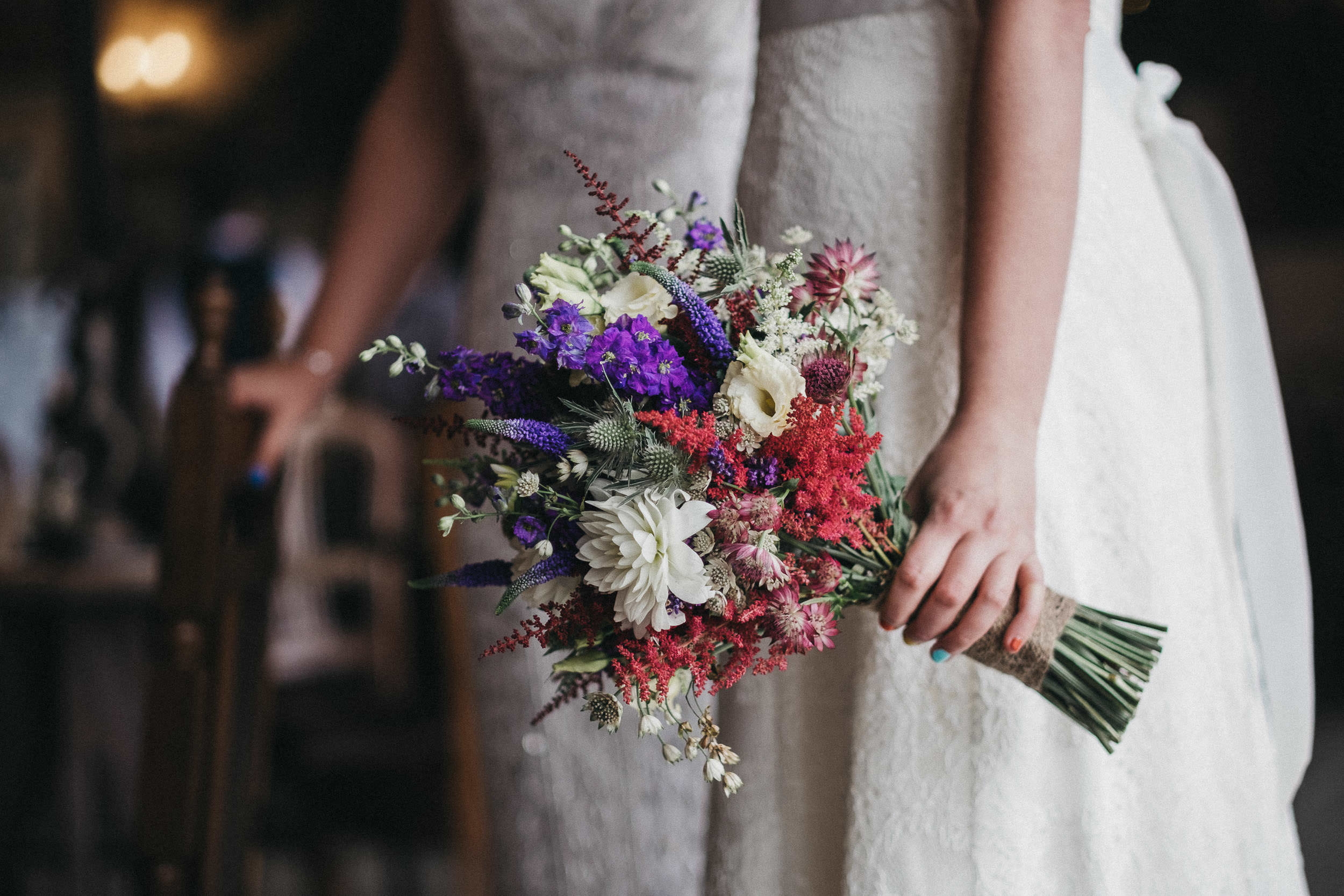 Close up of bride holding colourful flowers at the Old Barn South Causey Inn